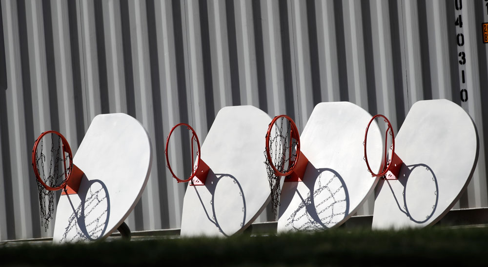 Basketball hoops and backboards, removed from city parks, sit in a row outside a storage facility as a statewide stay-at-home order remains in effect in an effort to reduce the spread of the virus on Monday, April 6, in Wheat Ridge, Colorado.