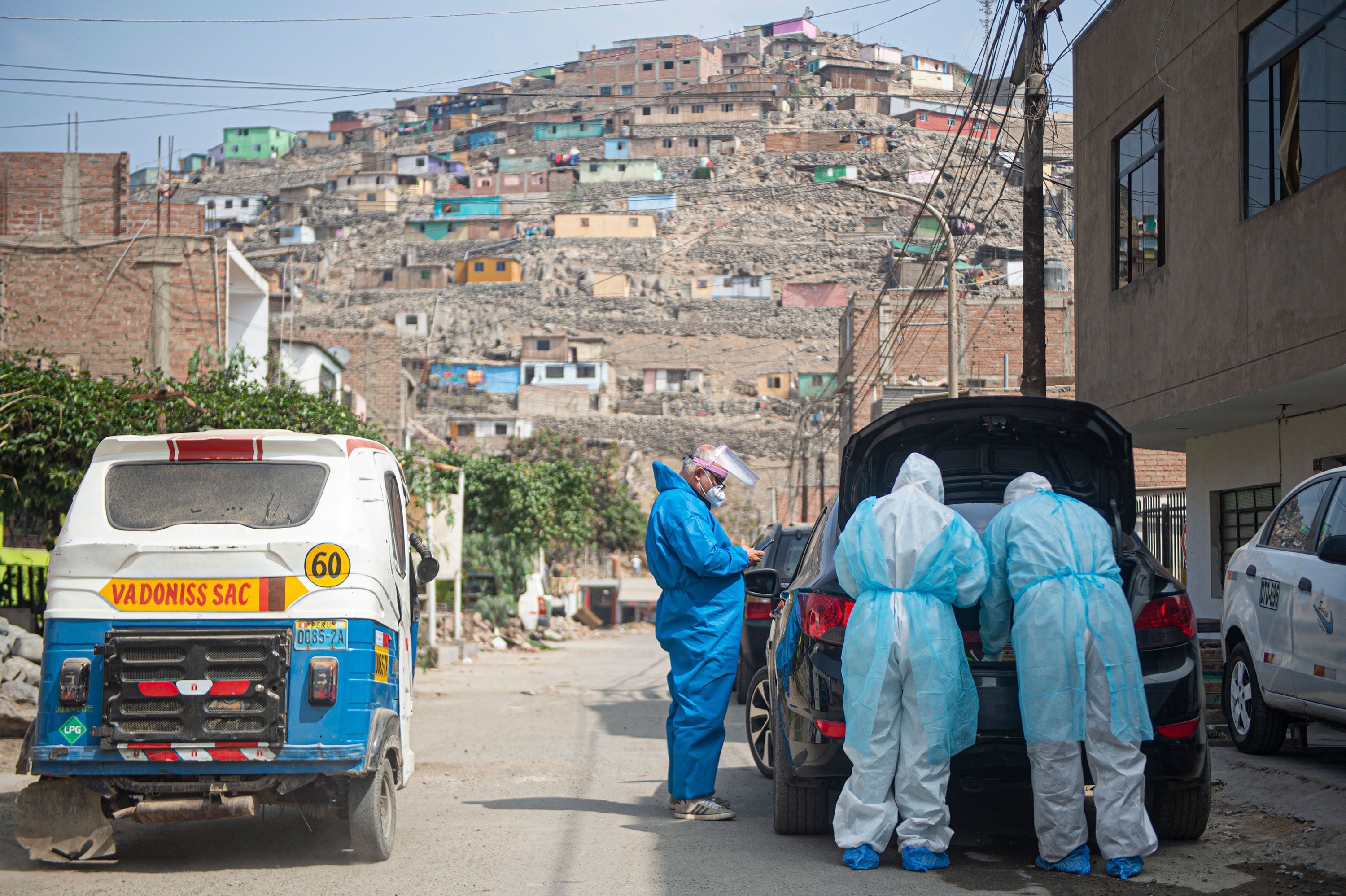 Doctors prepare to visit a coronavirus patient on the outskirts of Lima, Peru, on June 11.