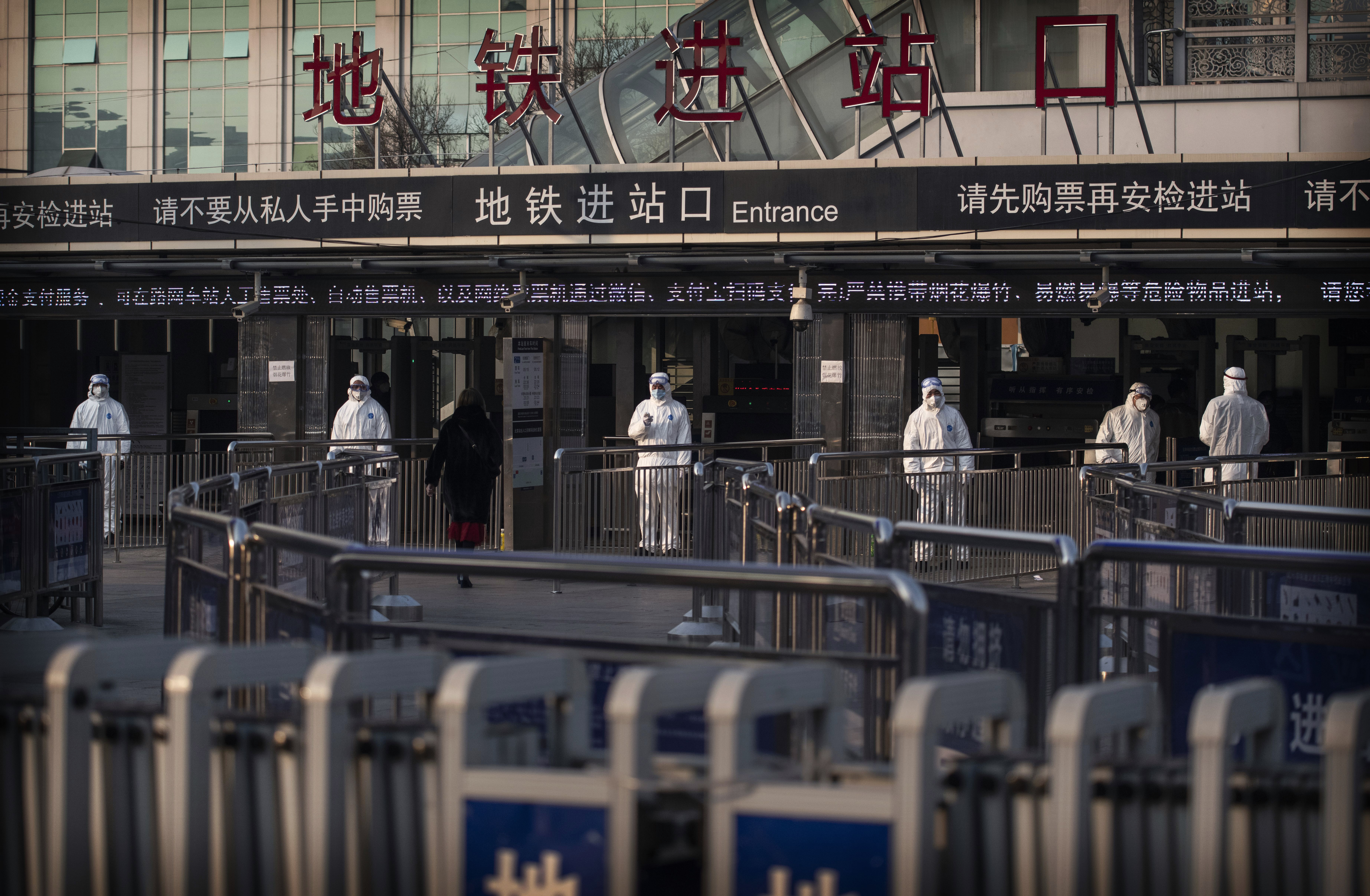 Chinese health workers standby to check the temperature of travelers entering a subway station in Beijing, China, on January 25.