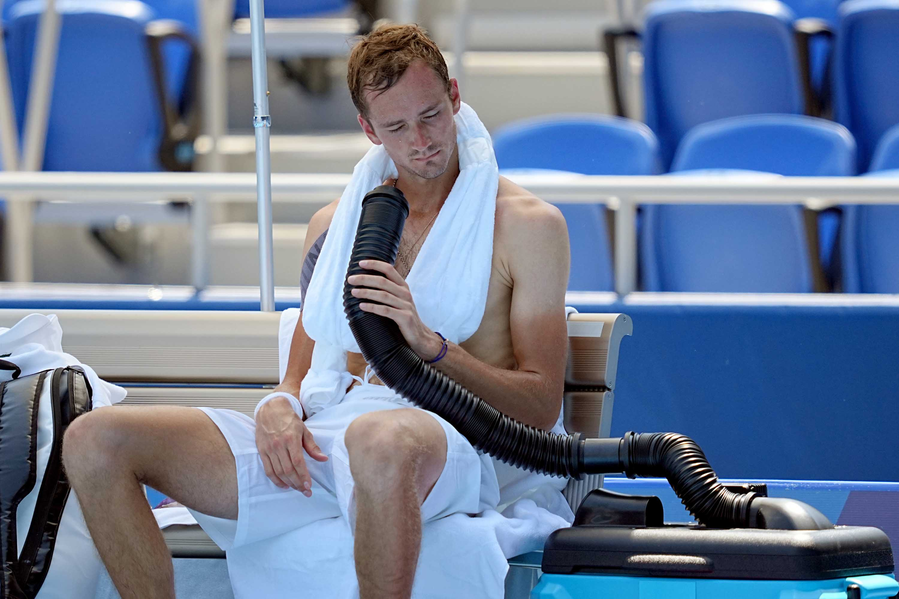 Daniil Medvedev cools down using a mobile air conditioner and a towel with ice cubes, during a break in the men's singles event in Tokyo, on July 24.