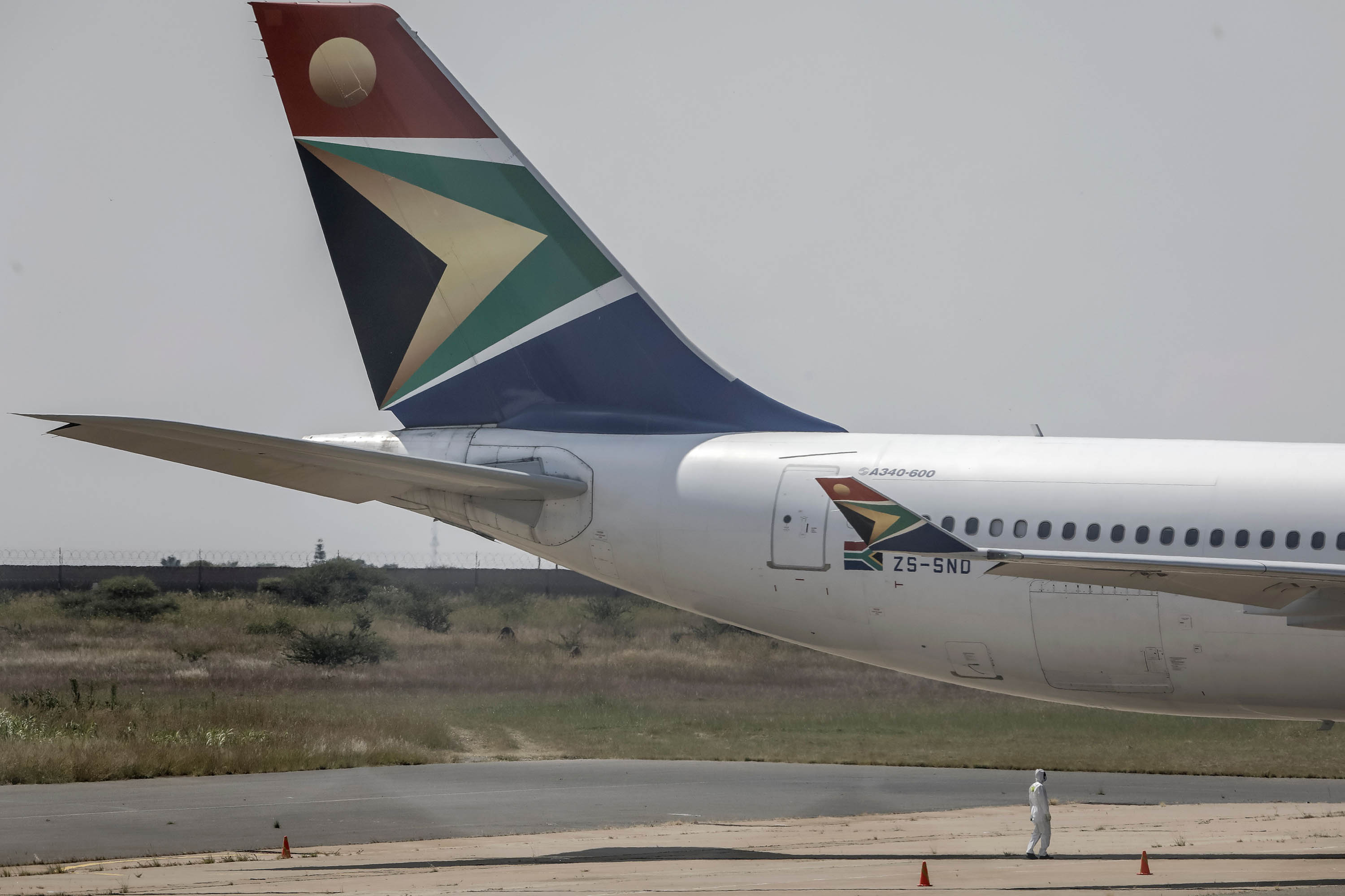 A worker wearing a protective suit stands below a South African Airways plane on March 14, as it arrives in Polokwane, South Africa.
