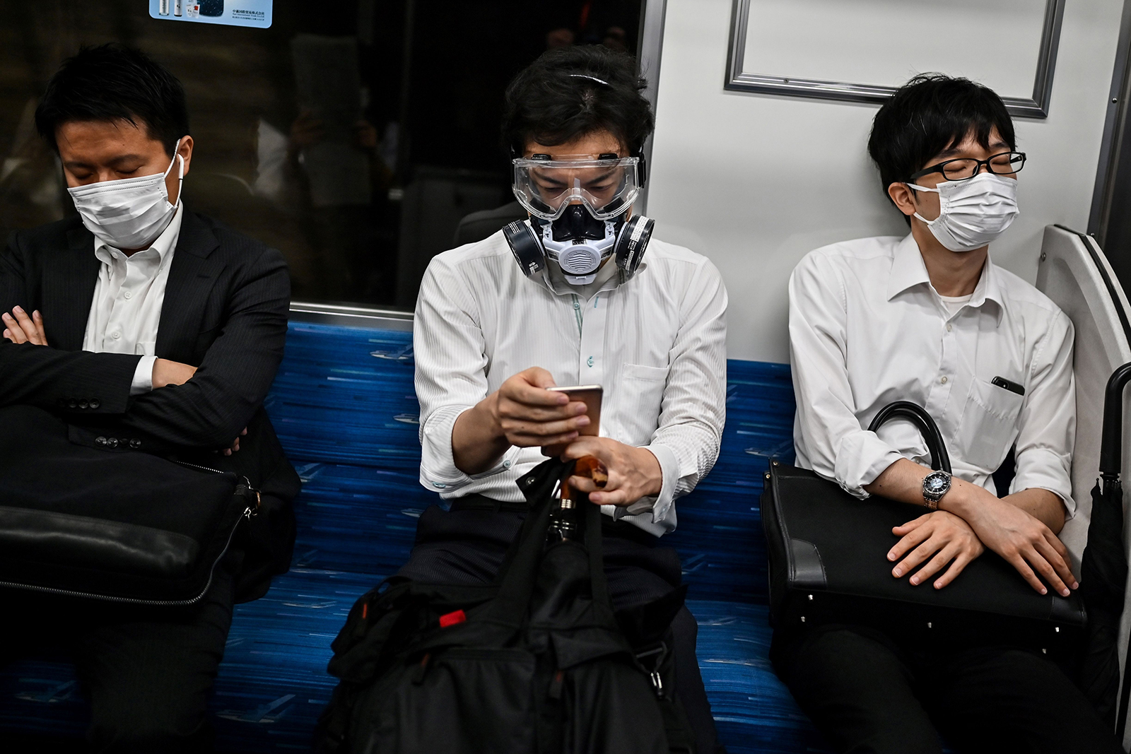 A man wearing a respirator and goggles sits in between commuters on a train in Tokyo on June 25.