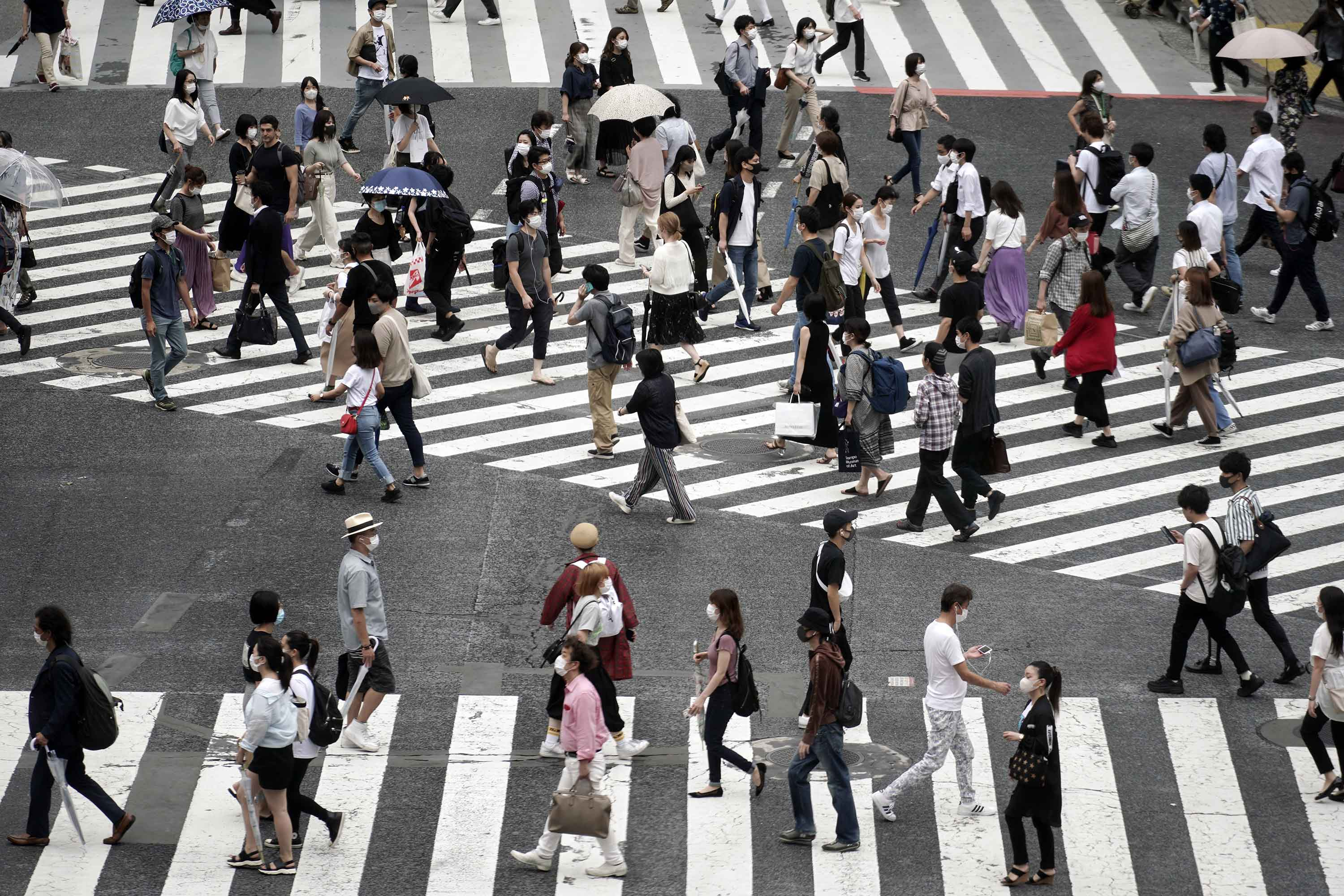 Pedestrians wearing face masks are seen at the Shibuya crossing in Tokyo, on Thursday, July 9.