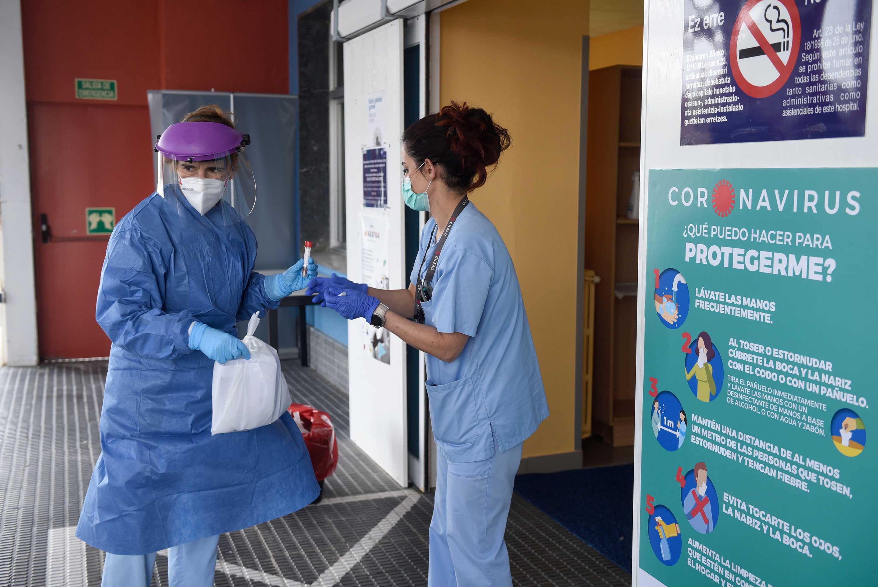 Health workers collect samples at a drive-through coronavirus testing center at Donostia Hospital in San Sebastian, Spain, on March 25.
