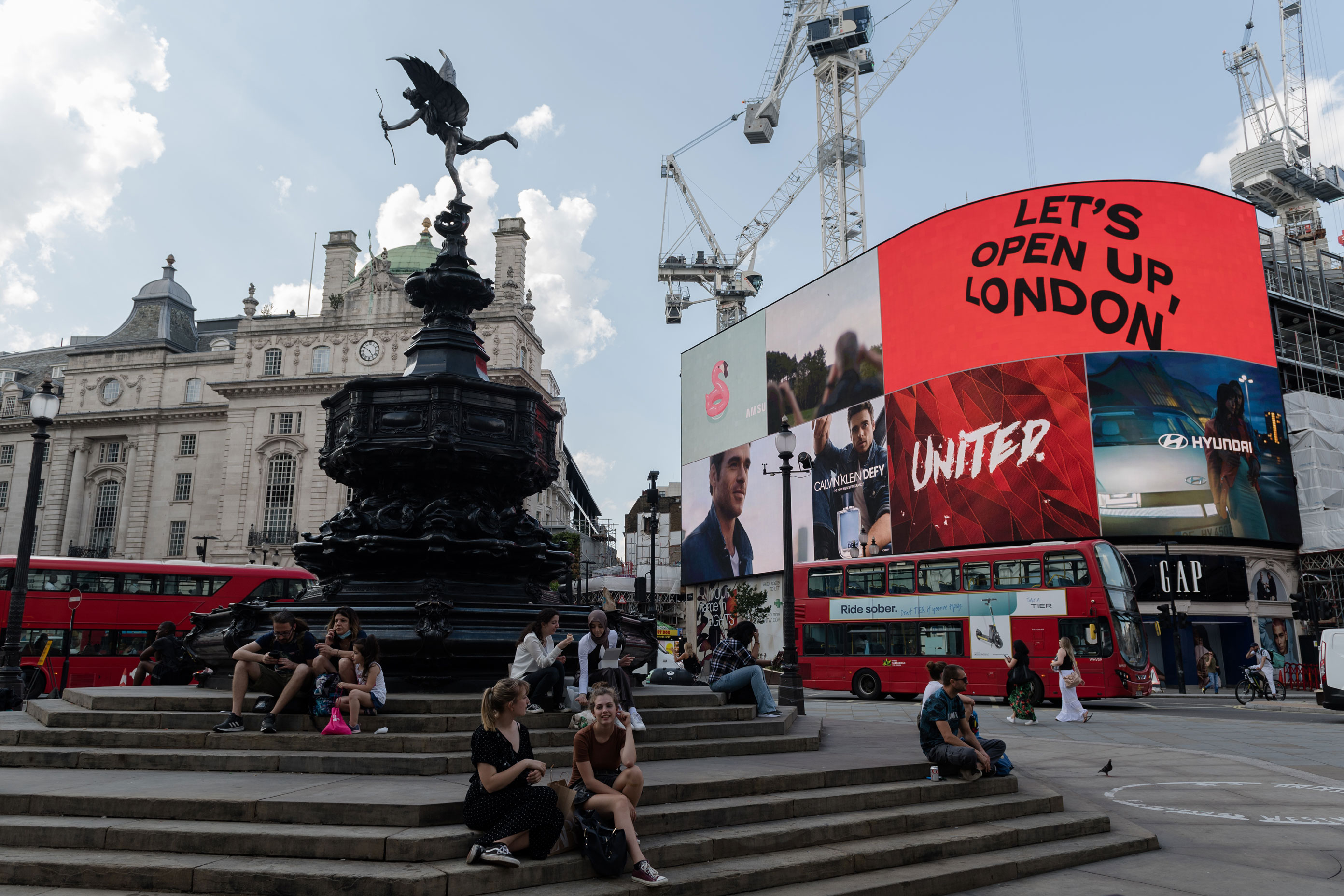 People sit in Piccadilly Circus as the light display reads 'Let's Open Up London' on the day of lifting of nearly all remaining coronavirus restrictions in London, on July 19.