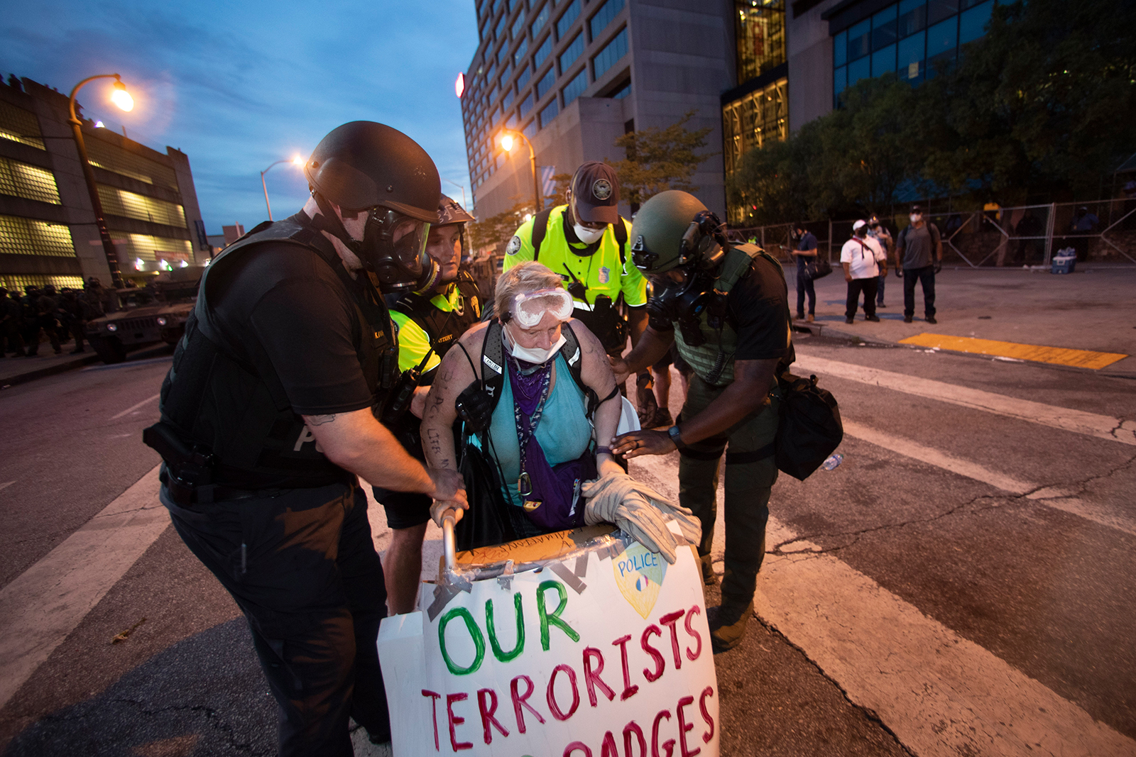 A woman is helped to her feet by police officers after she agreed to stop blocking a street during a protest, on June 3, in Atlanta.