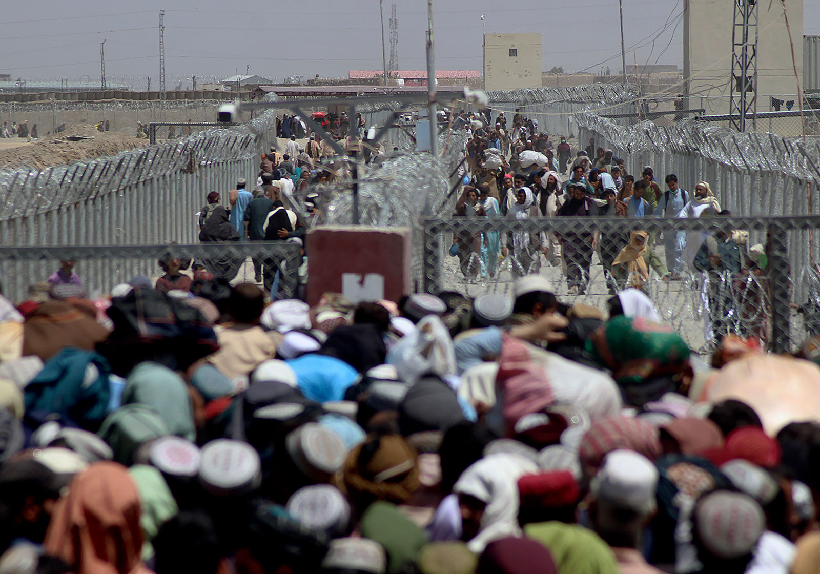 People cross the border between Pakistan and Afghanistan in Chaman, Pakistan, on Friday, August 13.