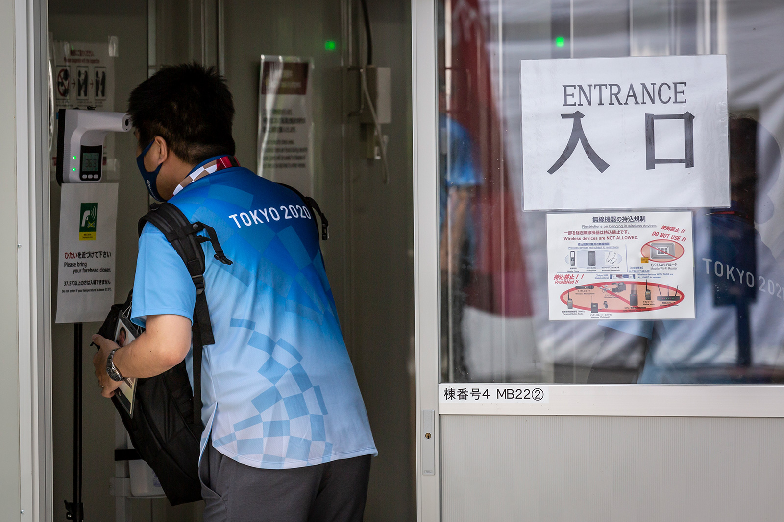 A volunteer has her body temperature checked at the entrance of Nippon Budokan on July 25 in Tokyo.