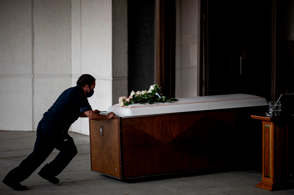 A worker pushes the coffin of Francia Nelly, from Ecuador, who died of complications related to Covid-19 inside the crematory after her funeral at the St. John Cemetery in Queens on June 5 in New York.
