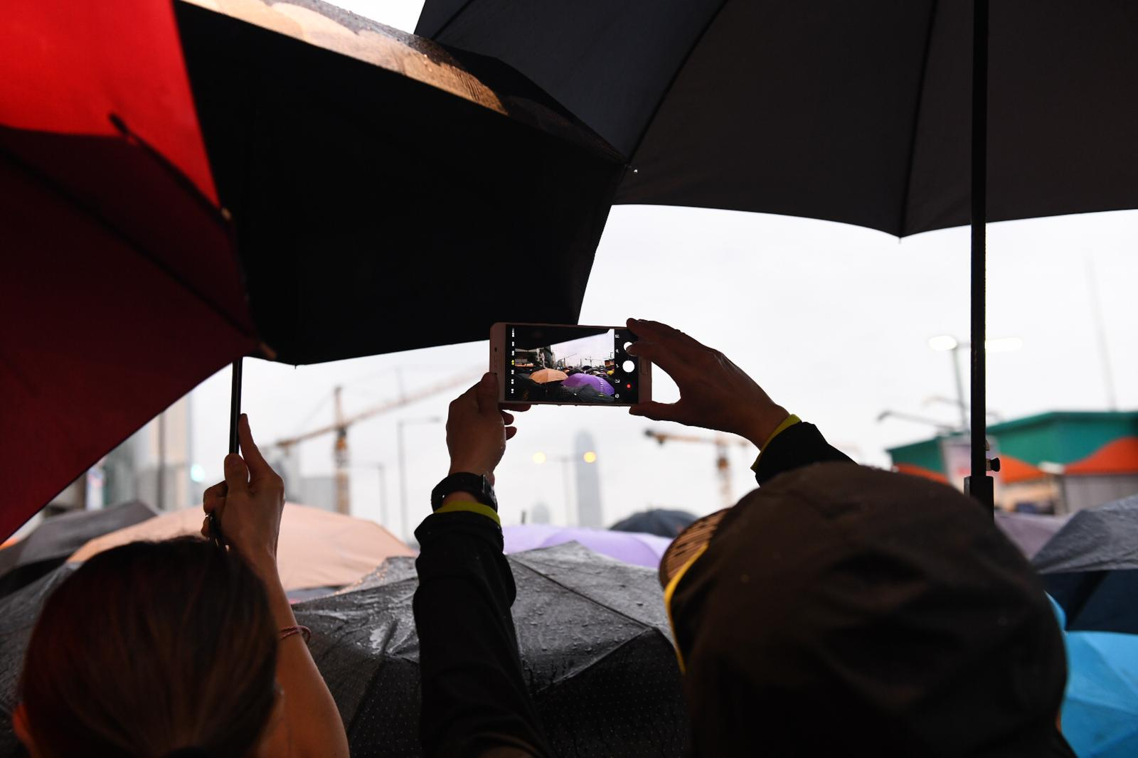 Protesters take photos as they shelter from the rain.