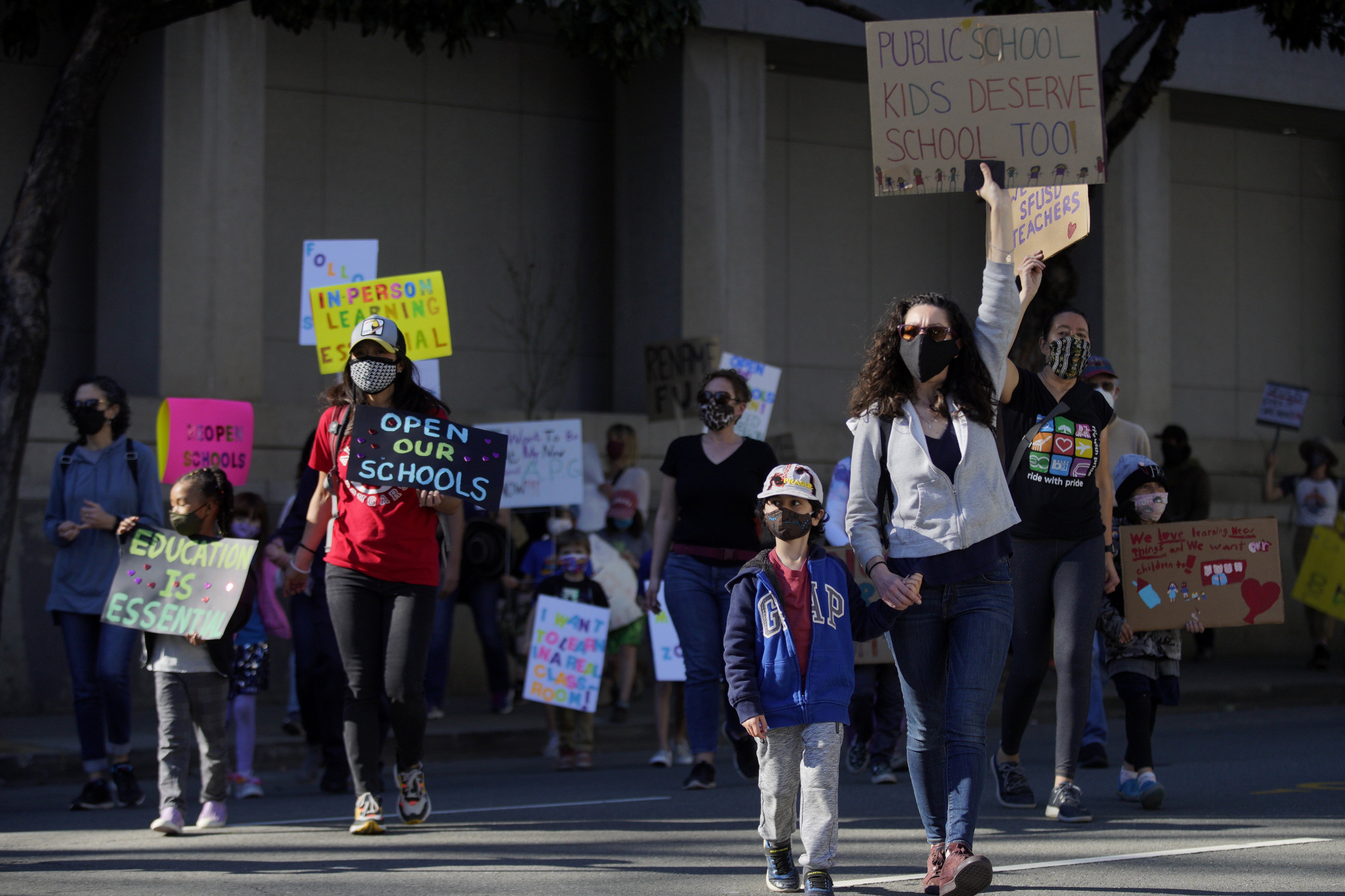 Hundreds of people march to City Hall in San Francisco, California, on February 6, to protest against remote learning and demand schools reopen in-person education.