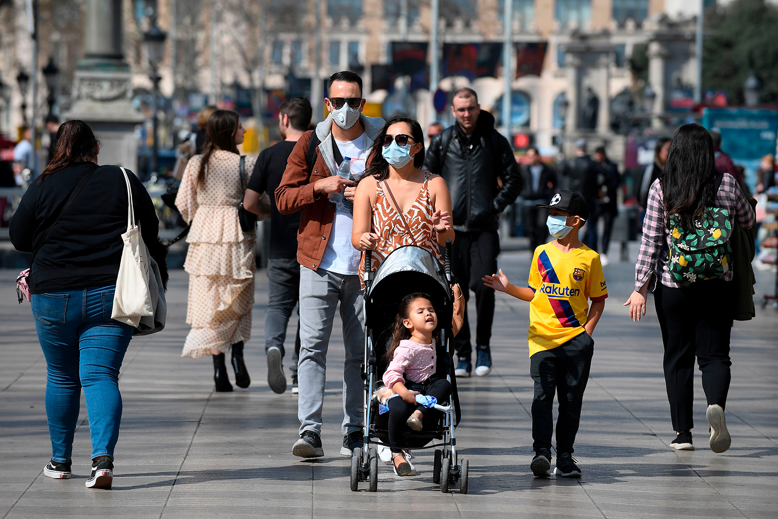 A family wearing protective masks walk in Barcelona on March 13.