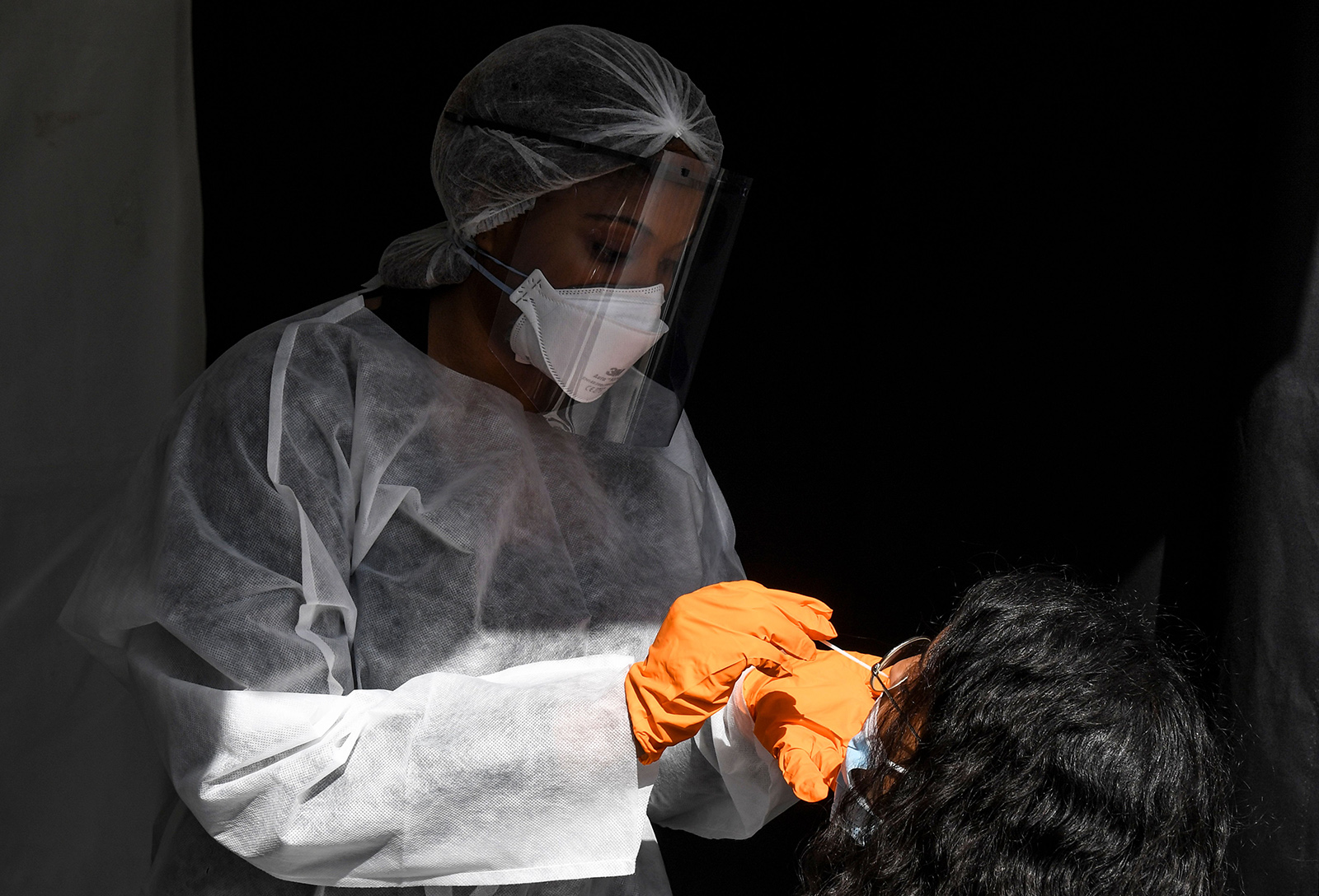 A medical worker wearing protective equipment uses a swab to do a PCR test for Covid-19 on a woman wearing a face mask in front of the city hall of Paris on August 31.