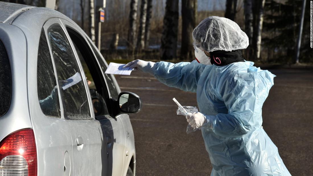 Medical workers take samples from patients at a coronavirus drive-in test center in Espoo, Finland in April.