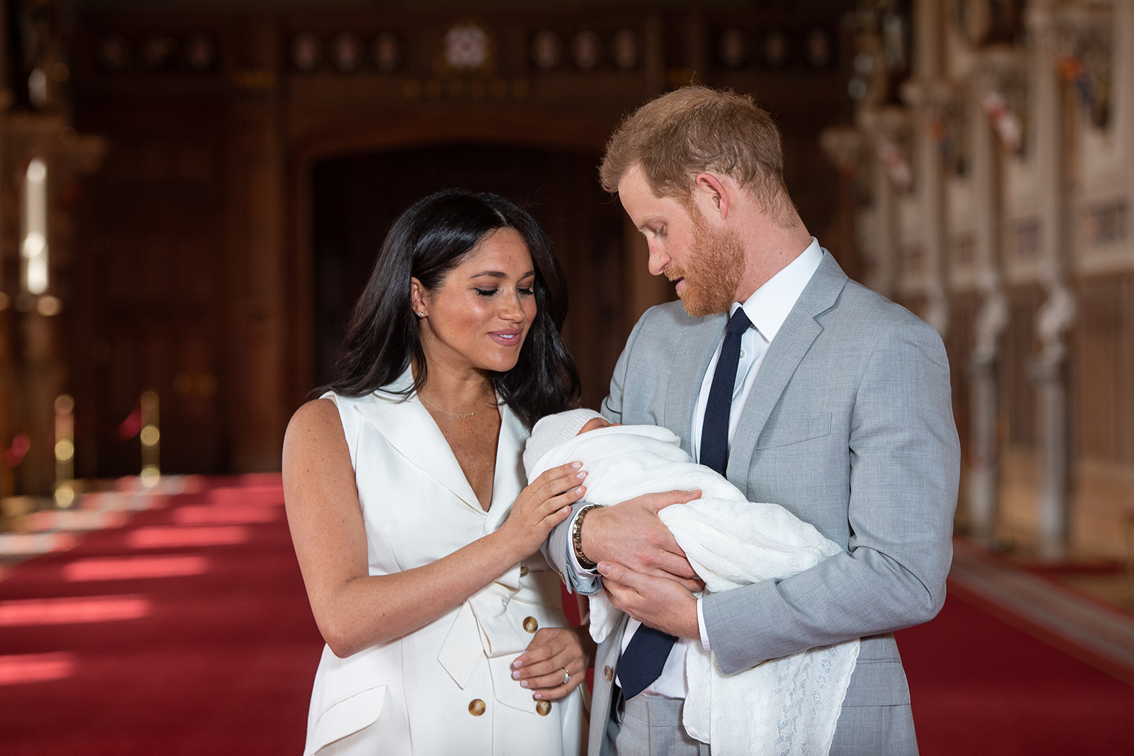 Prince Harry, Duke of Sussex and Meghan, Duchess of Sussex, pose with their newborn son Archie Harrison Mountbatten-Windsor during a photo call in St George's Hall at Windsor Castle on May 8, 2019 in Windsor, England.