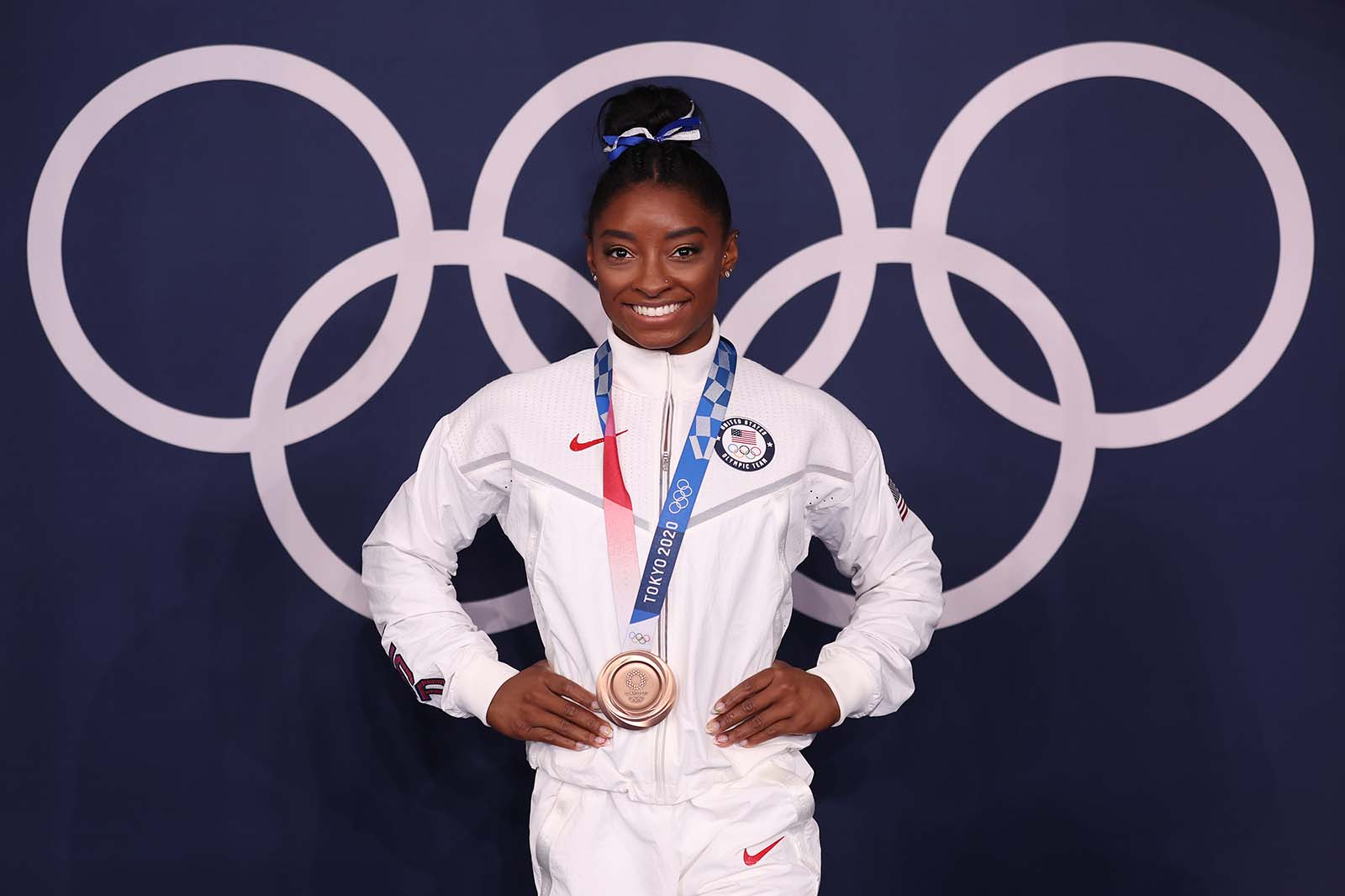 Simone Biles poses with her bronze medal following the women's balance beam final on August 3.