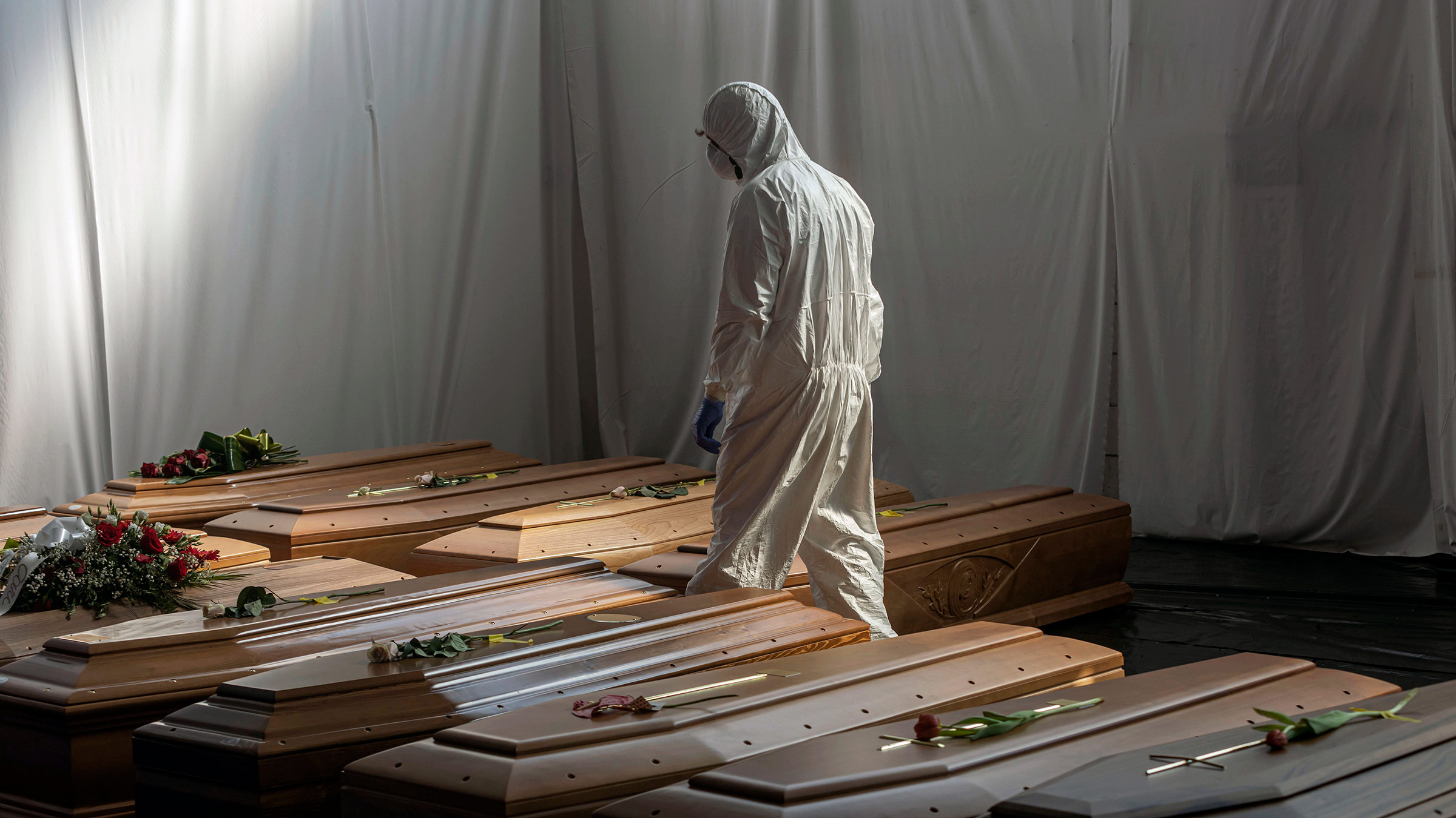 A Civil Protection member walks past the coffins of Covid-19 victims in Ponte San Pietro, Italy, on April 7, 2020.