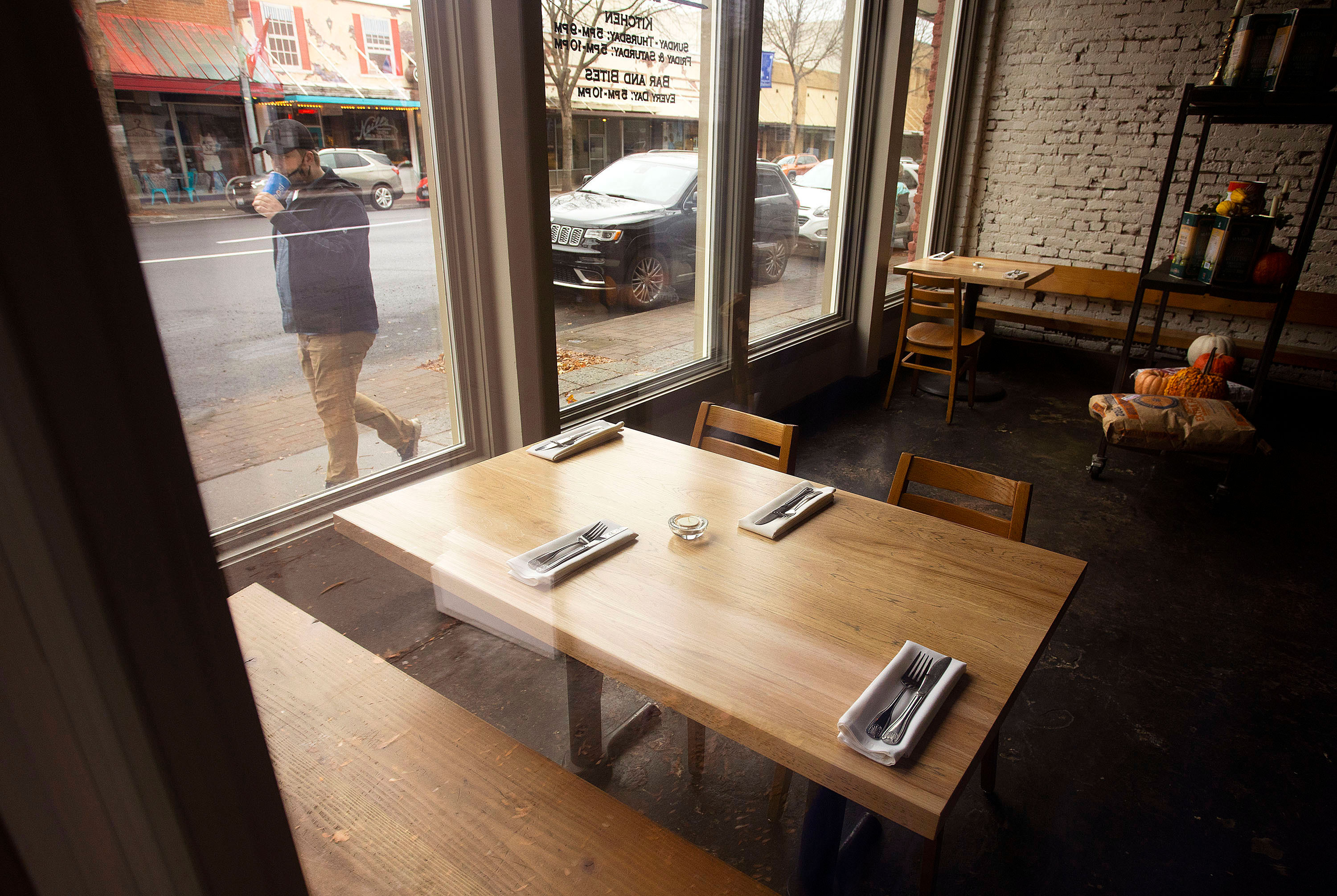 A person walks past empty tables at a restaurant and bar in Pullman, Washington, on November 16.