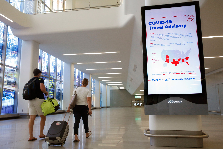 Arriving travelers walk through LaGuardia Airport on June 25 in New York.