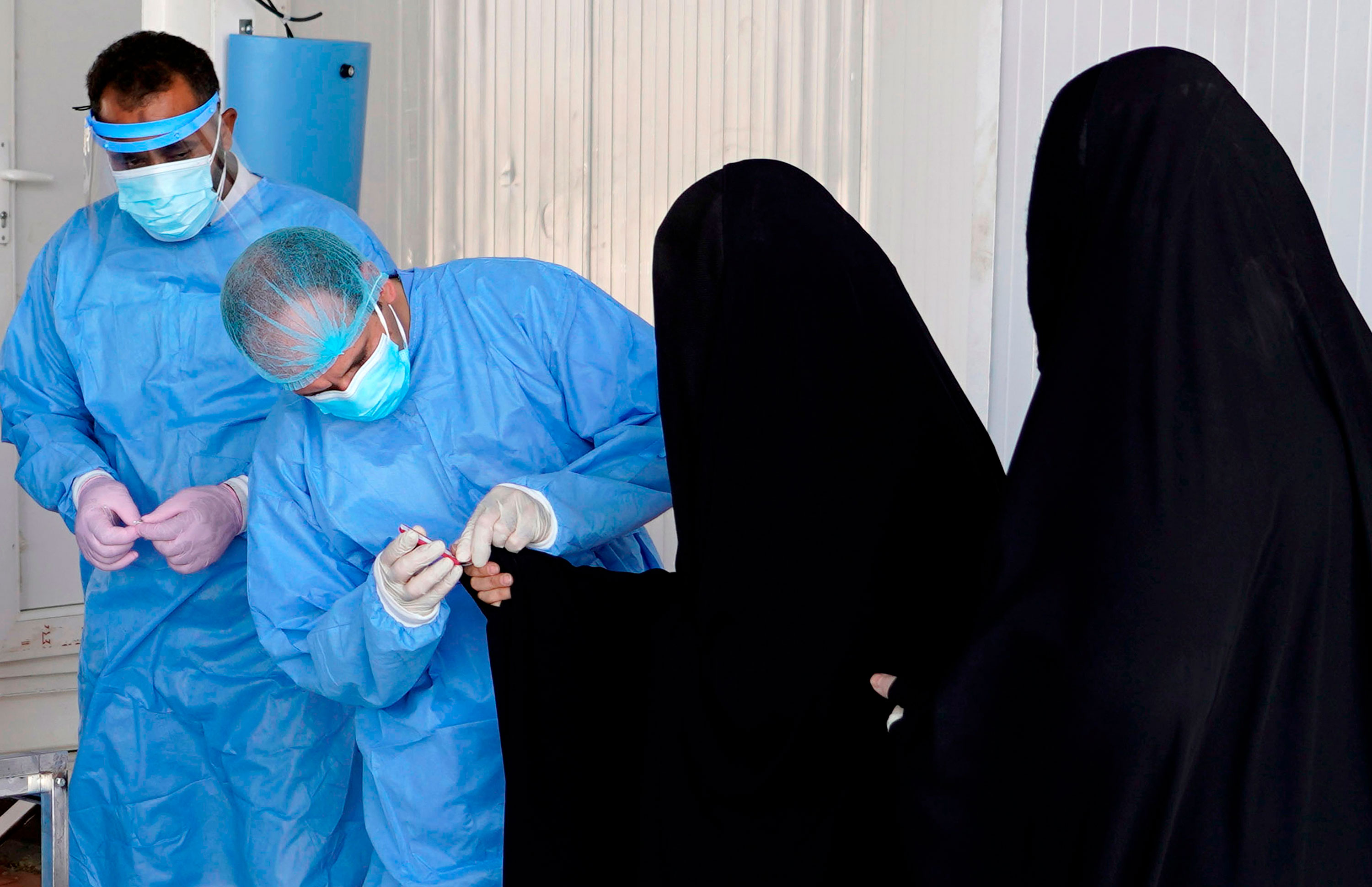 A health worker administers a coronavirus test at a testing facility Najaf, Iraq, on July 15.