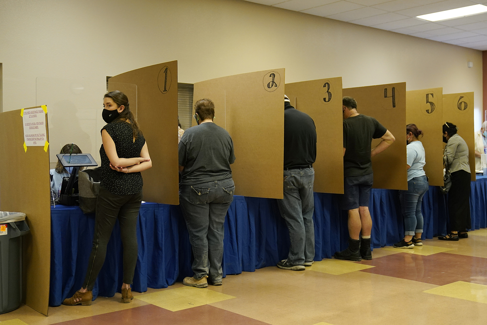 In this Oct. 30, 2020 file photo people prepare to vote at a polling place on the final day of early voting, in Las Vegas.