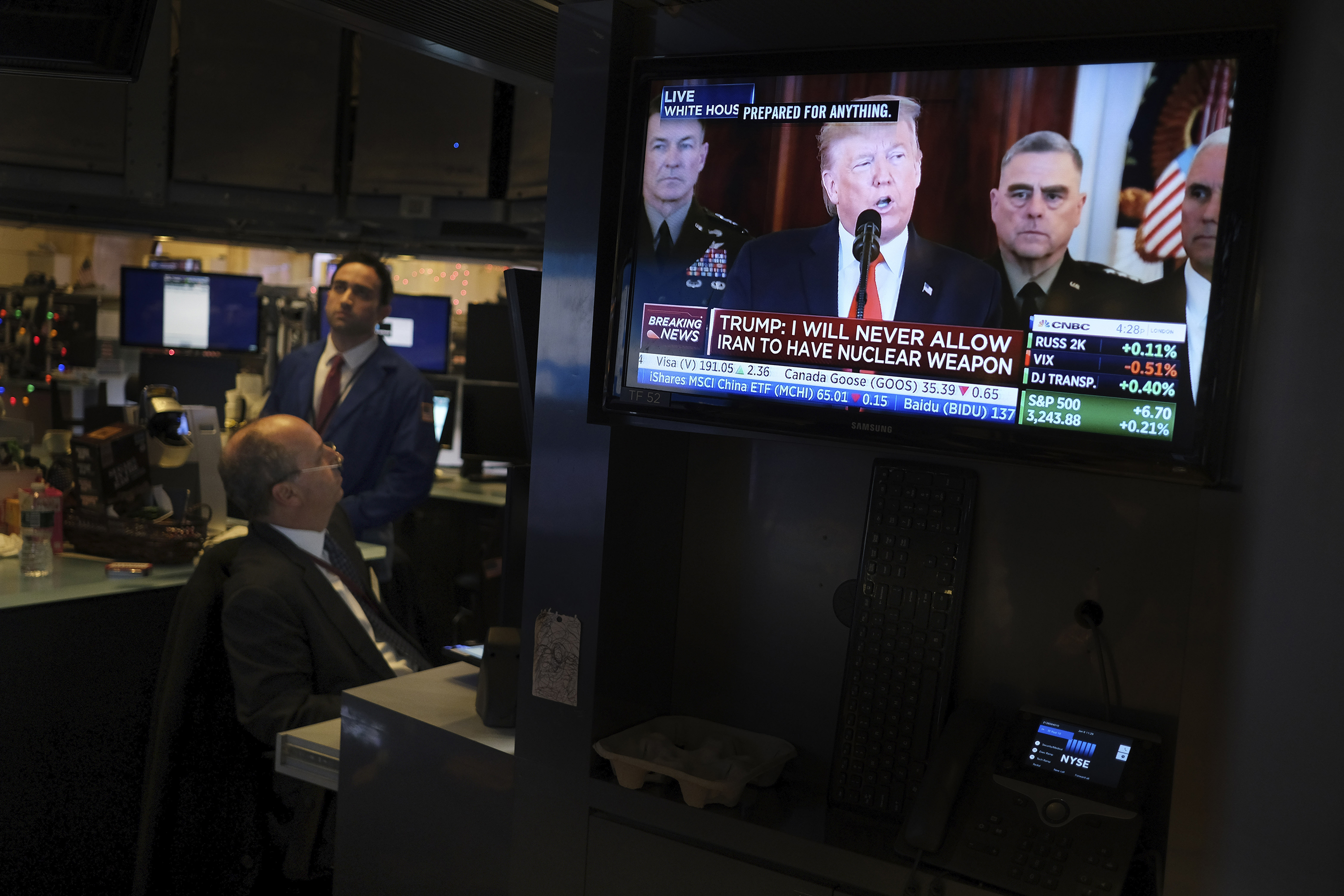 Traders pause to watch a televised speech by President Donald Trump as they work the floor of the New York Stock Exchange on Wednesday, January 8.