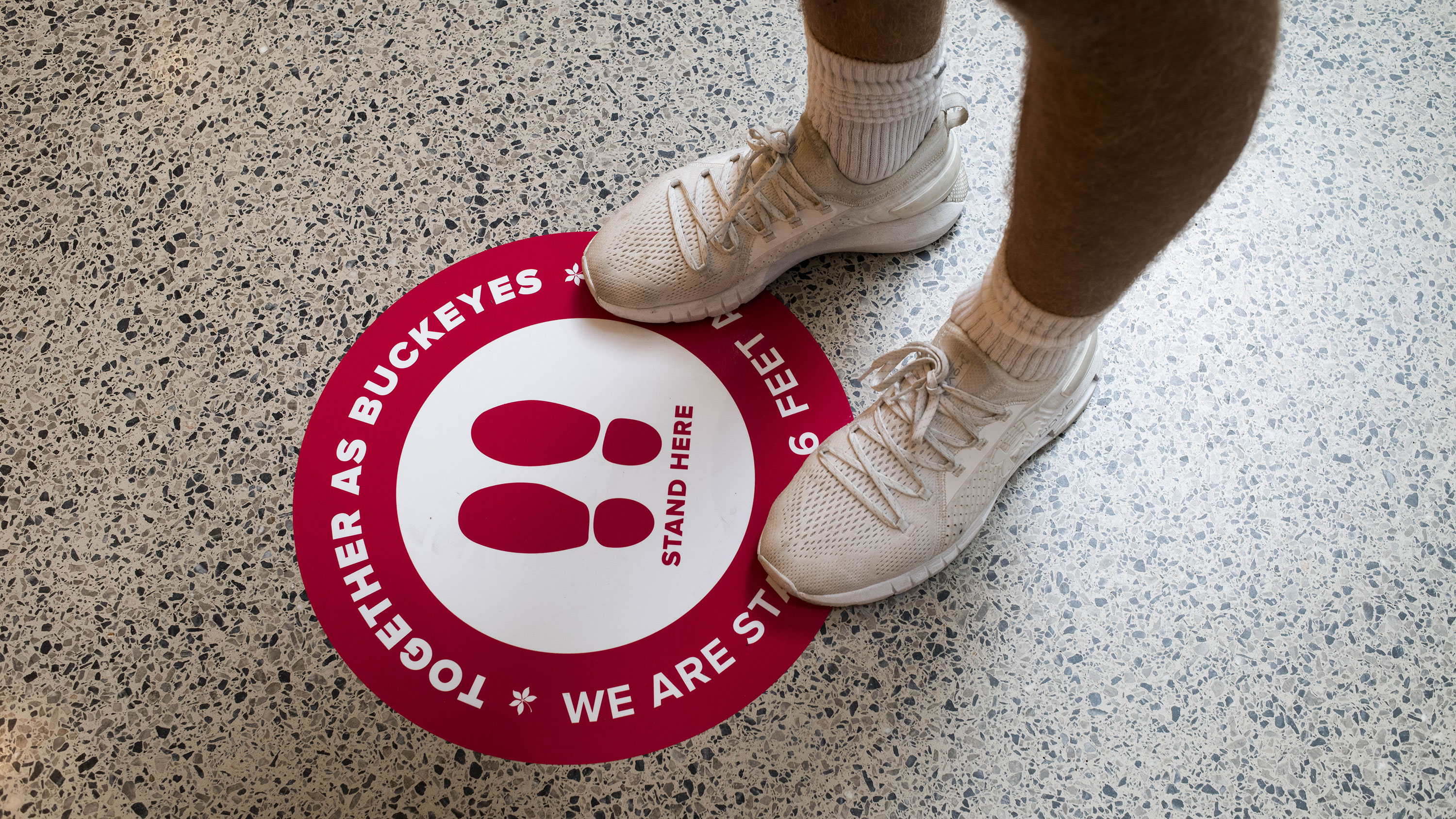 A student stands on a socially distancing marker while waiting in line inside the Thompson Library on the first day of classes at Ohio State University in Columbus, Ohio, on August 25.