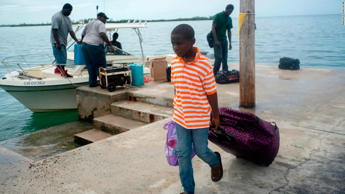 A child evacuated from a nearby Cay due to the danger of floods drags his suitcase when he arrives on a ship at the port before the arrival of Hurricane Dorian in Sweeting's Cay, Grand Bahama, Bahamas, Saturday.