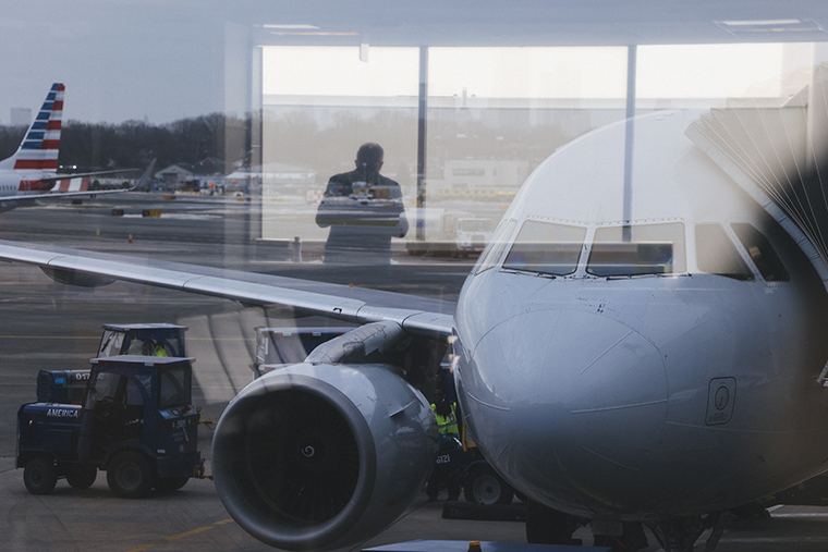 A traveler is reflected in a window at LaGuardia Airport (LGA) in New York, U.S., on Thursday, Dec. 24, 2020.