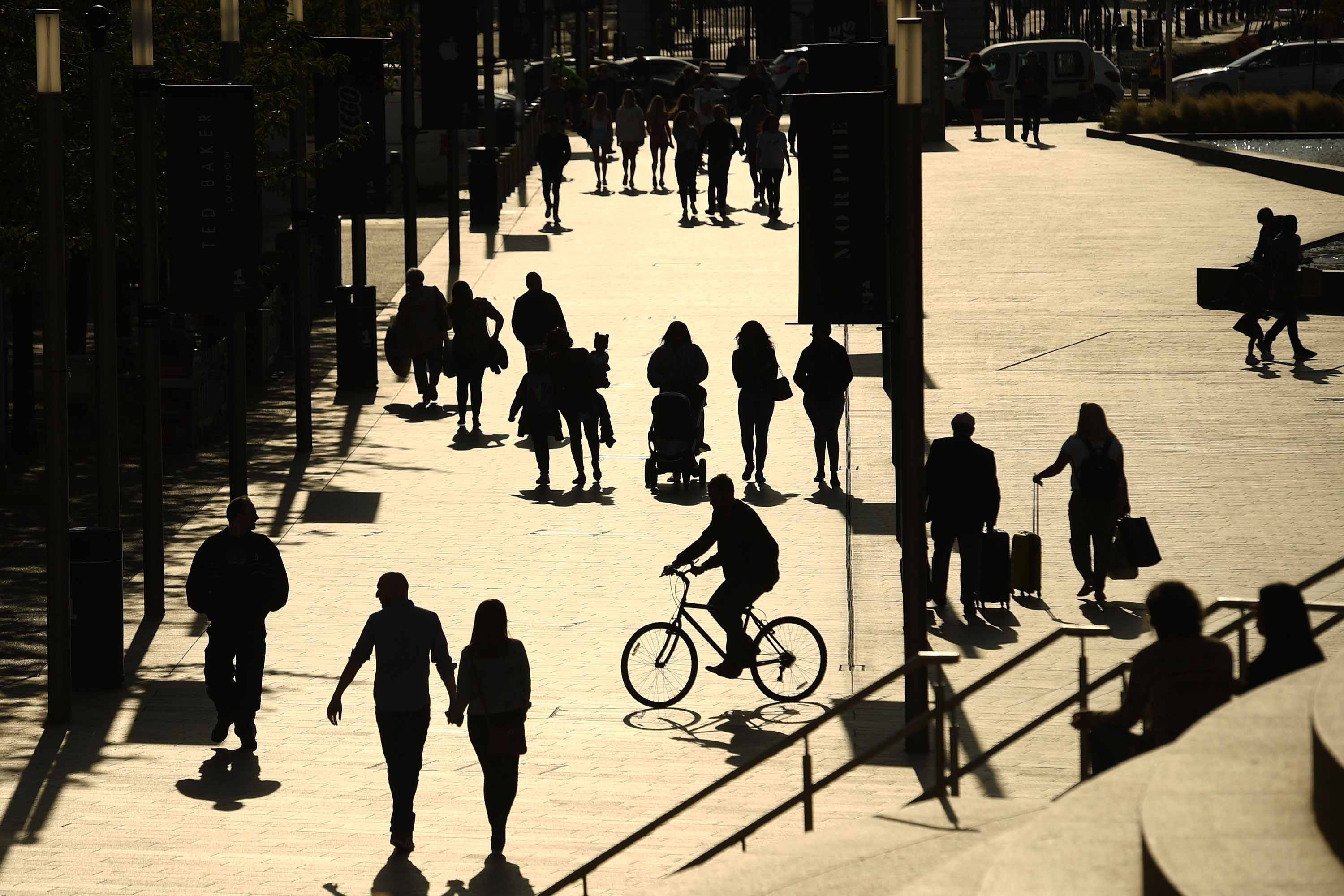 People are silhouetted against the late summer sun in Liverpool, England on September 18, after the British government imposed fresh restrictions on the city following a rise in coronavirus cases.