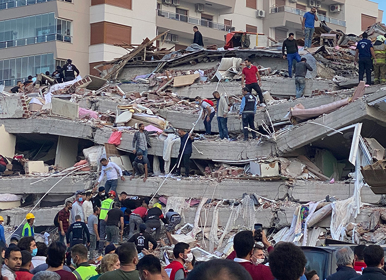 Rescue workers and local people try to save residents trapped in the debris of a collapsed building, in Izmir, Turkey, Friday, Oct. 30, 2020.