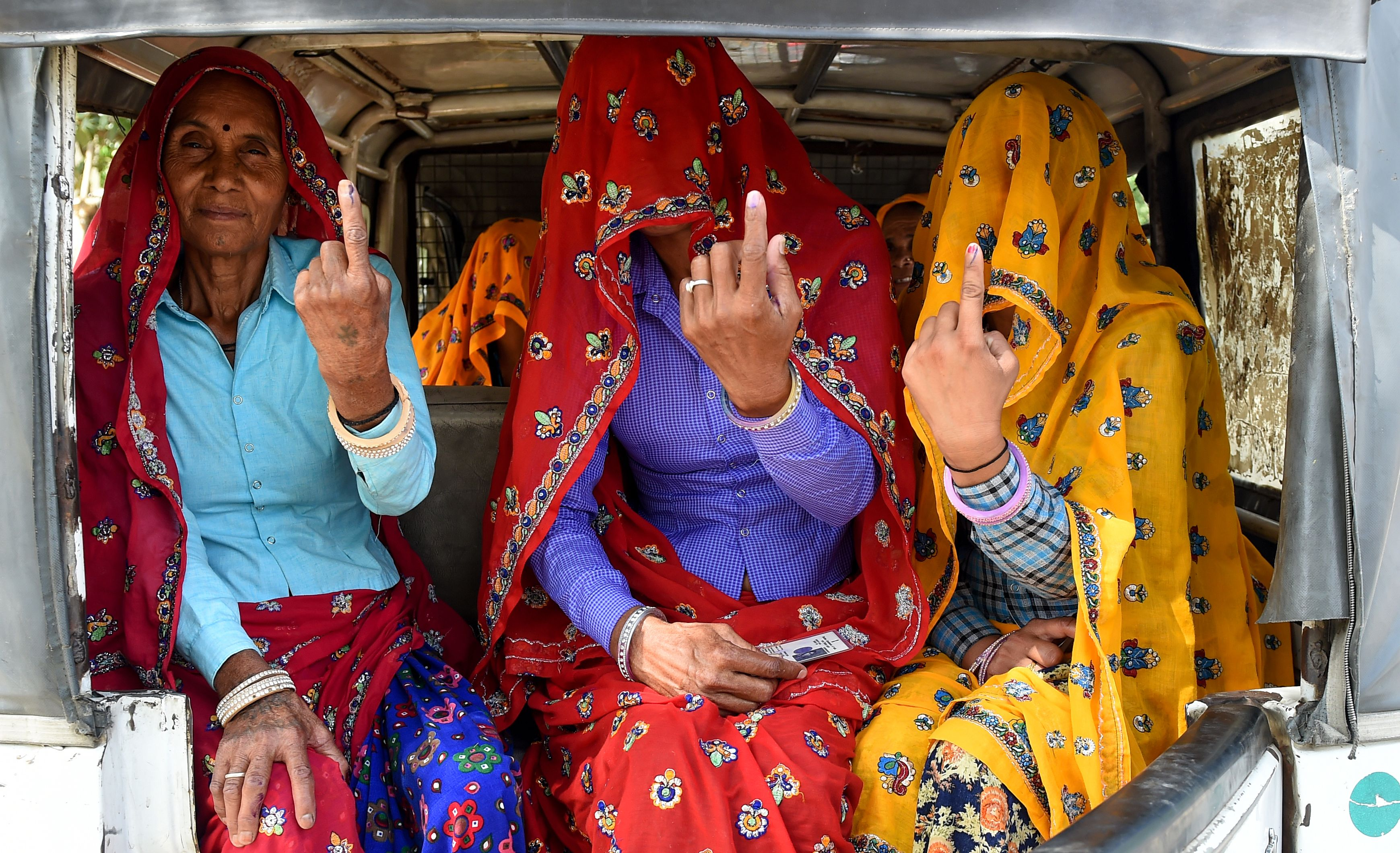 Indian women sit inside an auto-rickshaw as they show their ink-marked fingers after casting their vote in Alwar in the northern Indian state of Rajasthan on May 6, 2019.
