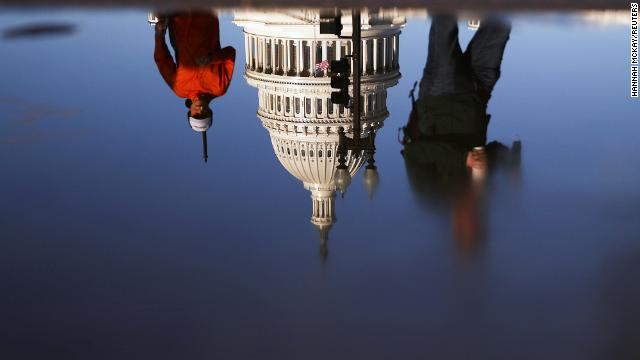 The U.S. Capitol building is seen reflected in a puddle in Washington, on November 10.