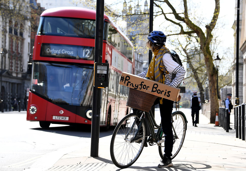 A woman shows a sign on her bicycle as British Prime Minister Boris Johnson is in intensive care fighting the coronavirus in London, Tuesday, April 7.