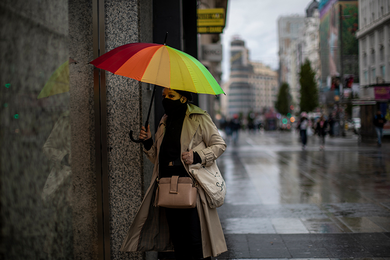 A woman wearing a face mask holds an umbrella in central Madrid, Spain, on Thursday.
