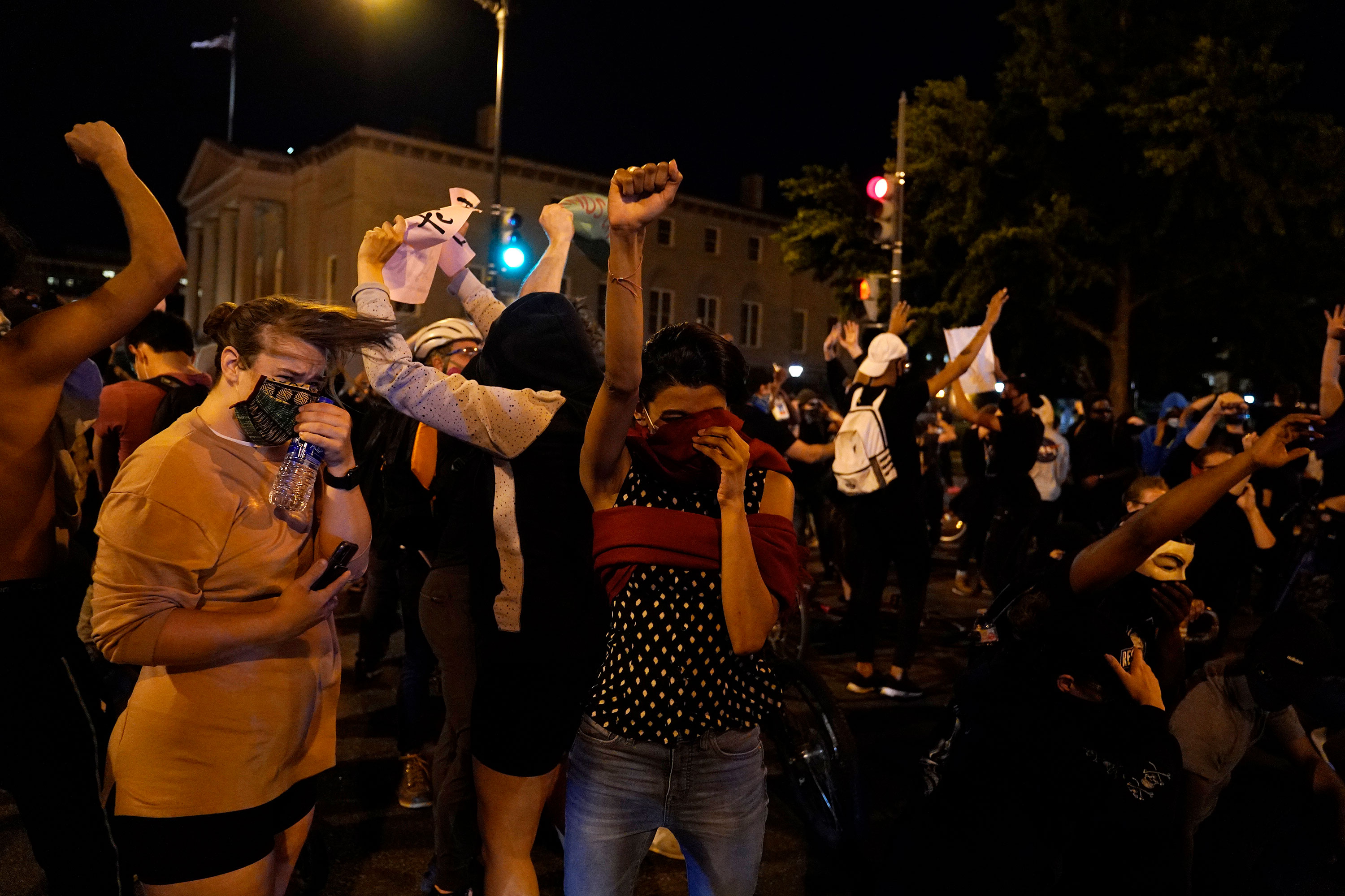 Demonstrators react as a helicopter circles low overhead near the White House in Washington on June 1.