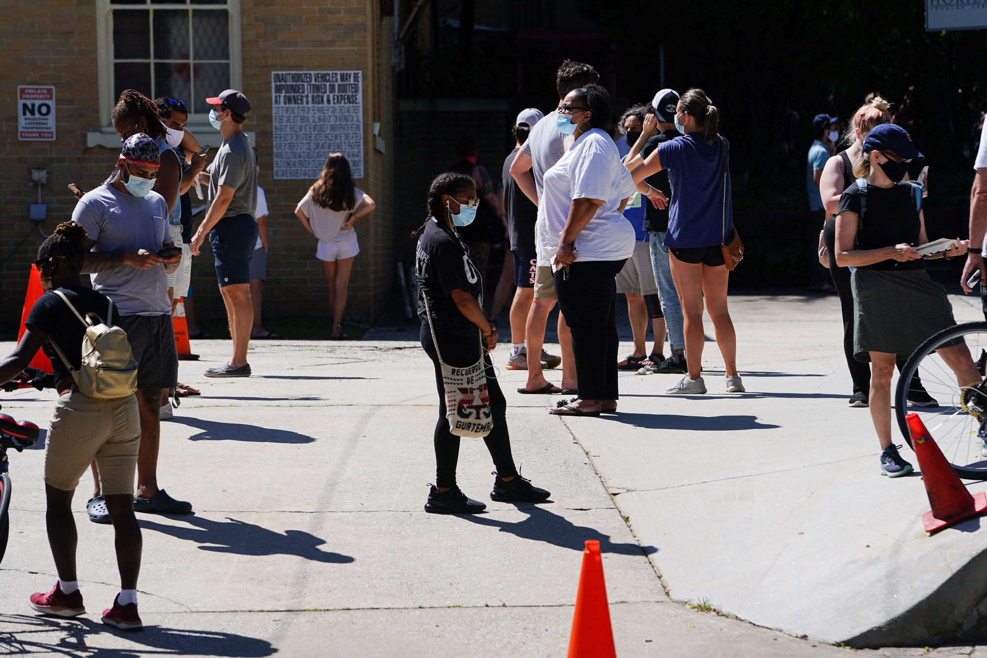 People stand in line to get tested for COVID-19 at a free walk-up testing site on July 11 in Atlanta.