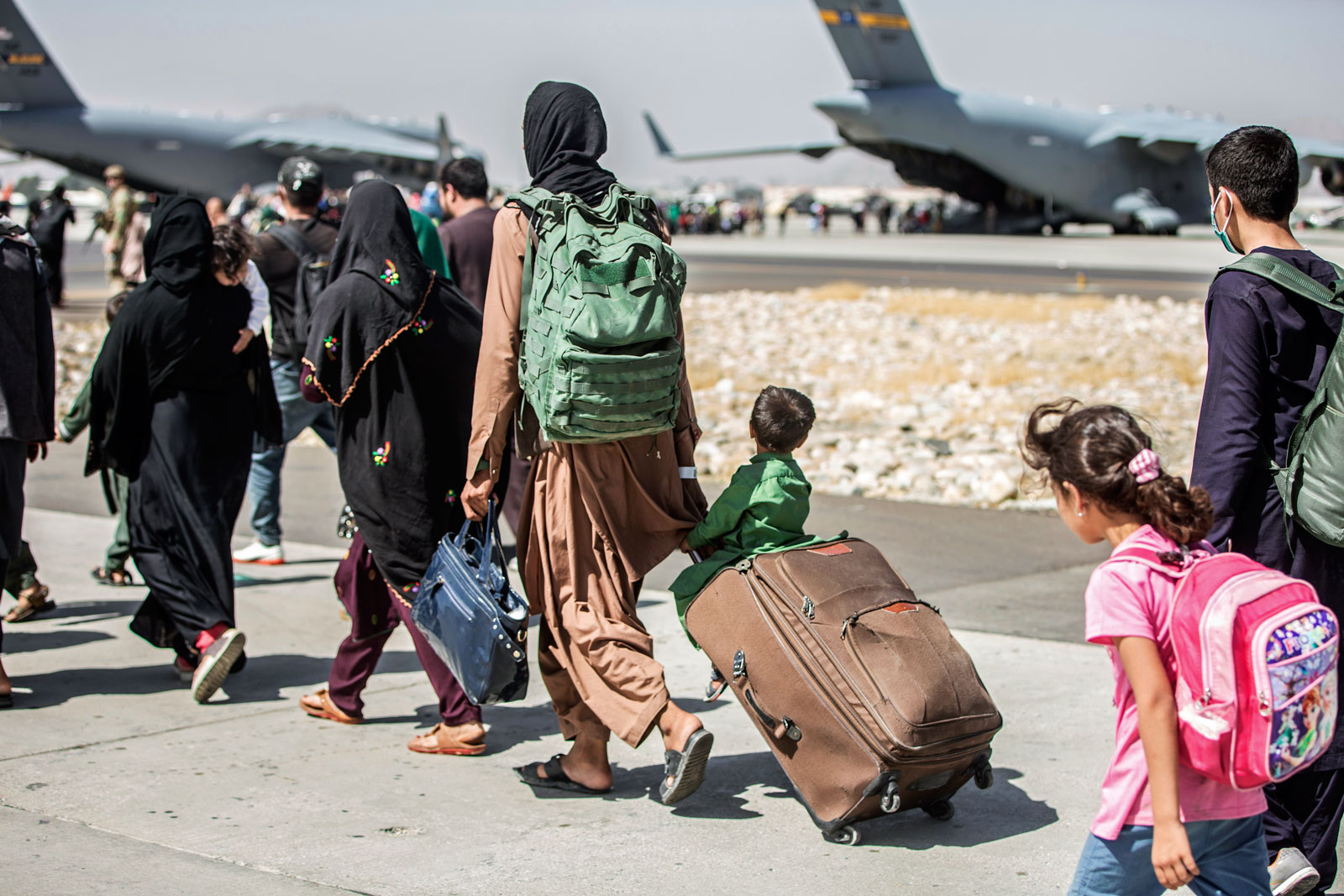 In this photo provided by the U.S. Marine Corps, families walk towards their flight during ongoing evacuations at Hamid Karzai International Airport, in Kabul, Afghanistan on August 24.