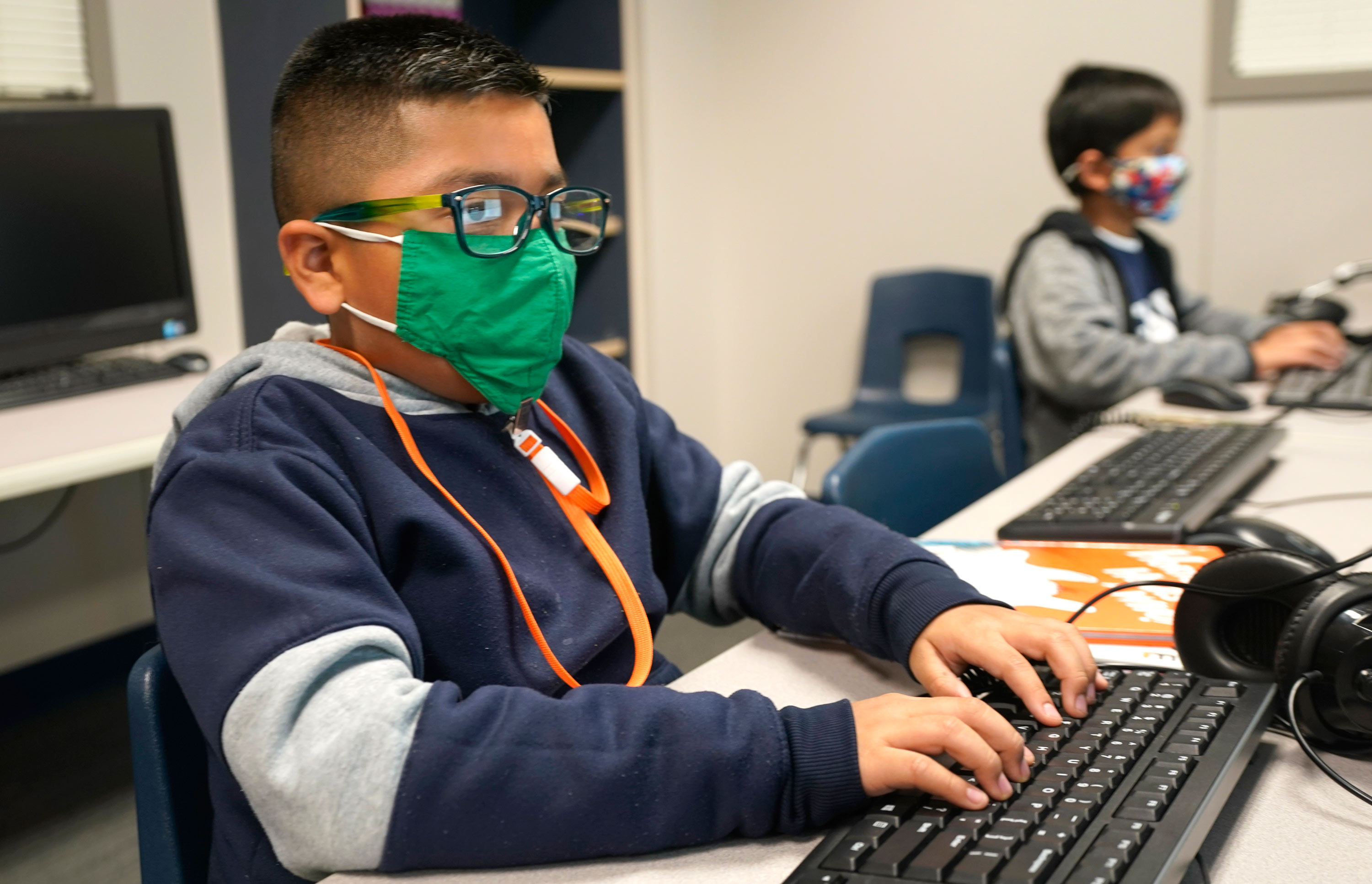 Students wearing face masks work on computers at Tibbals Elementary School in Murphy, Texas, on December 3, 2020.