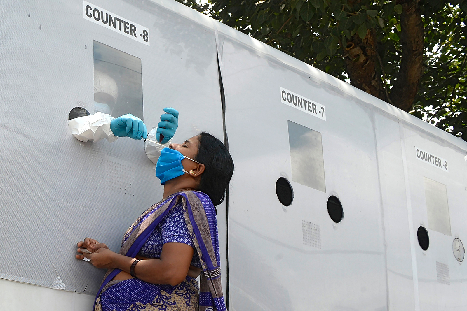 A health worker wearing personal protective equipment collects a swab sample of a woman at a free Covid-19 testing site in Hyderabad, India, on August 25.