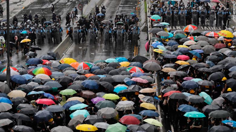 Protesters holding umbrellas face off police officers in anti-riot gear in Hong Kong on Monday, July 1, 2019.