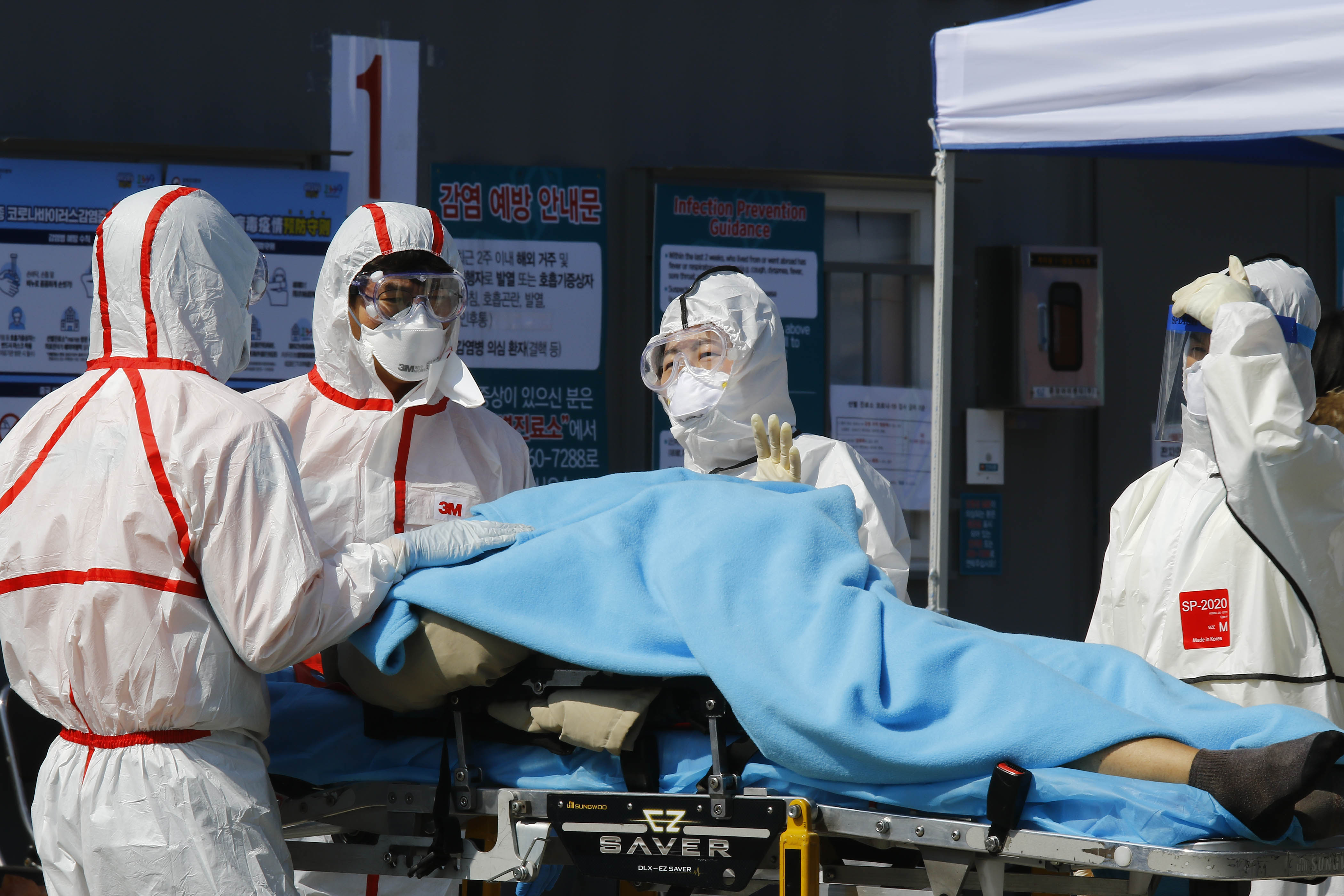 A coronavirus patient is moved at a medical center in Daegu, South Korea, on Monday.