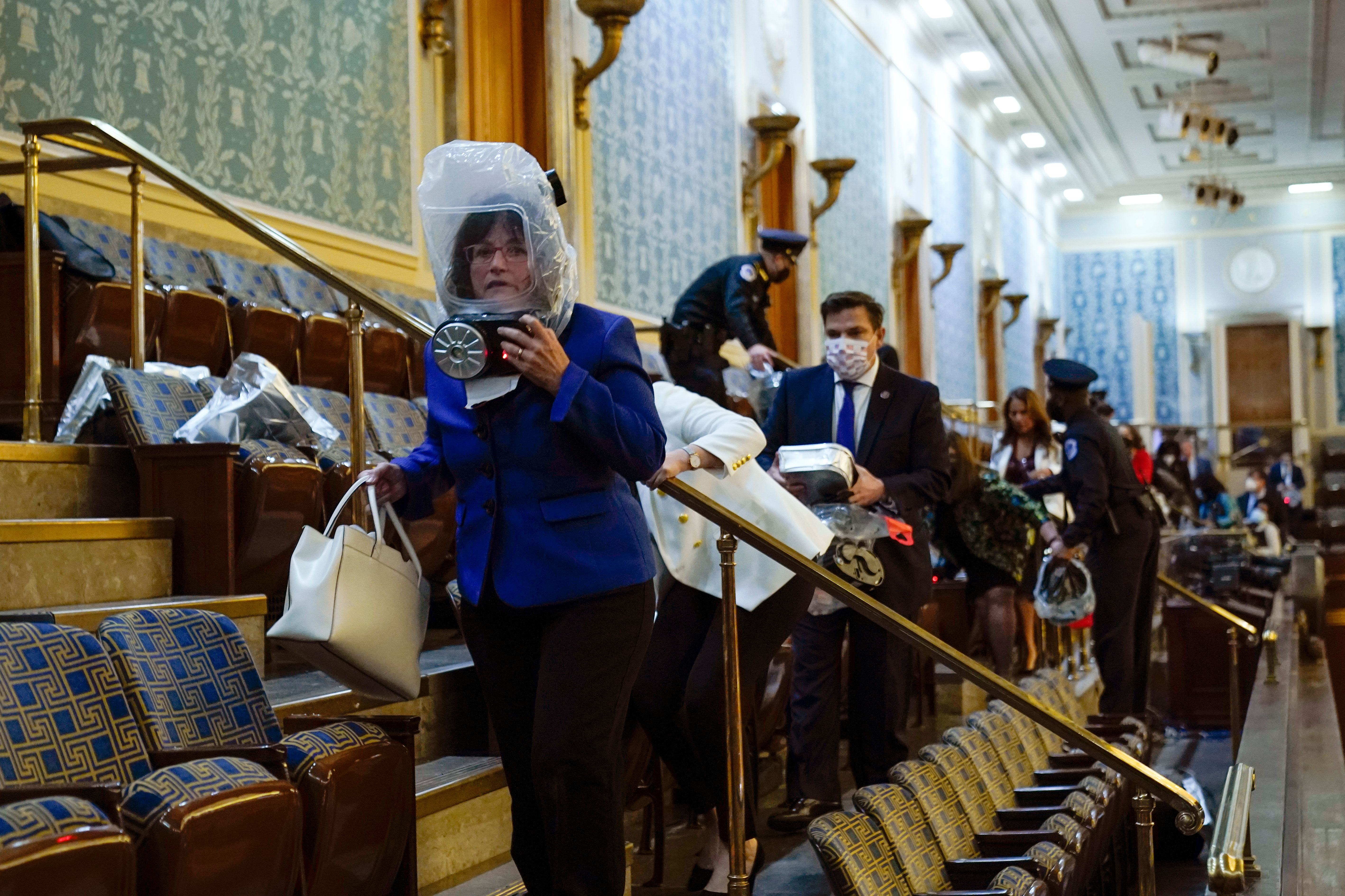 New Hampshire Rep. Annie Kuster, pictured at front in blue, shelters in the House gallery as pro-Trump rioters try to break into the Chamber at the Capitol on January 6.