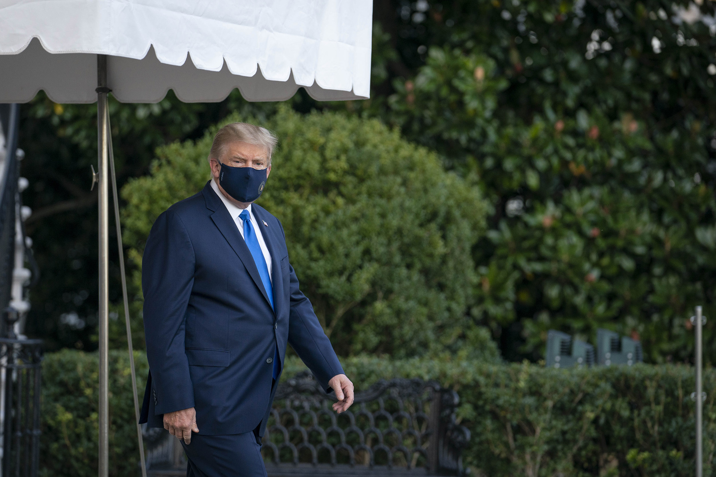 President Donald Trump wears a mask while walking to the South Lawn of the White House before boarding Marine One in Washington, D.C., U.S., on Friday, Oct. 2, 2020.