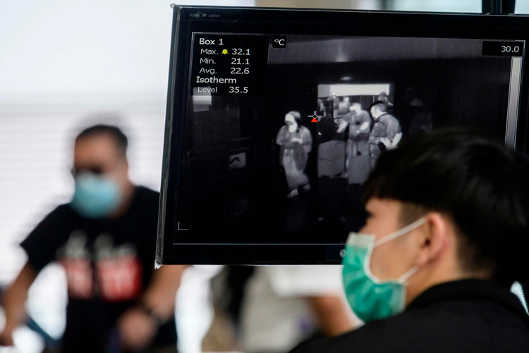 A airport employee worker monitors a thermal screening display as passengers enter Hong Kong's Chek Lap Kok International Airport on March 10.