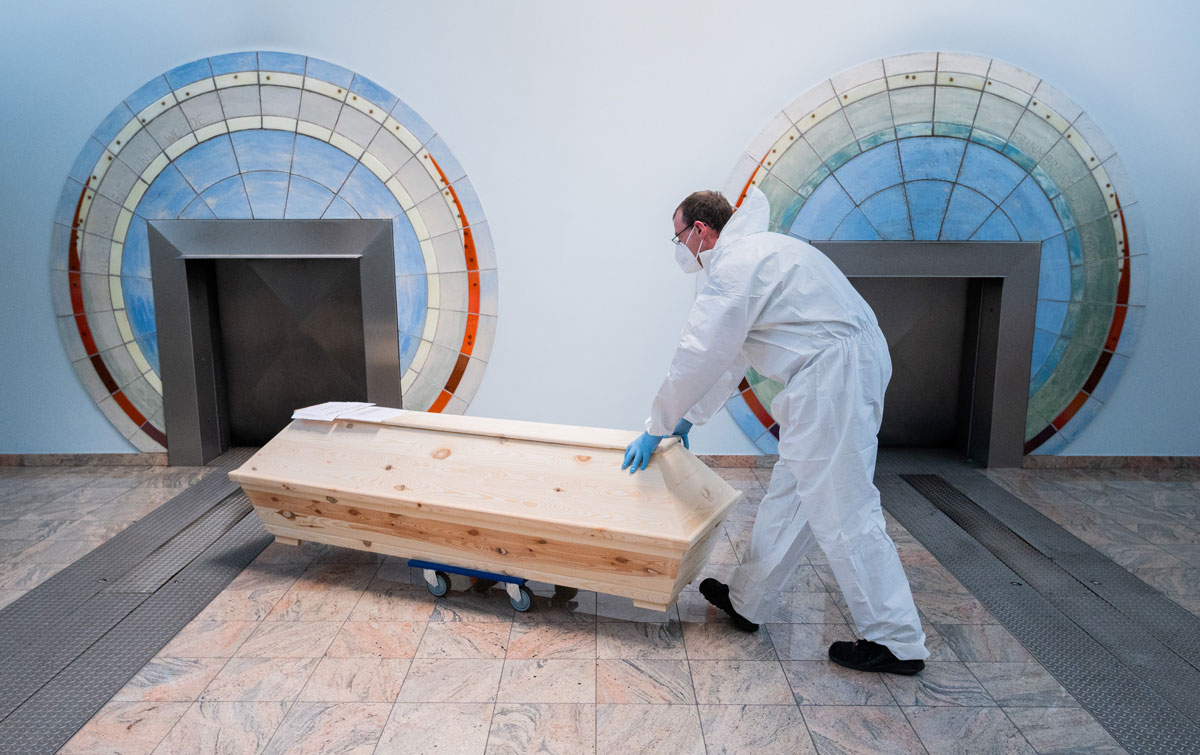"""A cremation technician brings a deceased person in a coffin labelled """"SARS-CoV-2 positive Corona"""" for cremation at Giesen, Germany on April 28."""