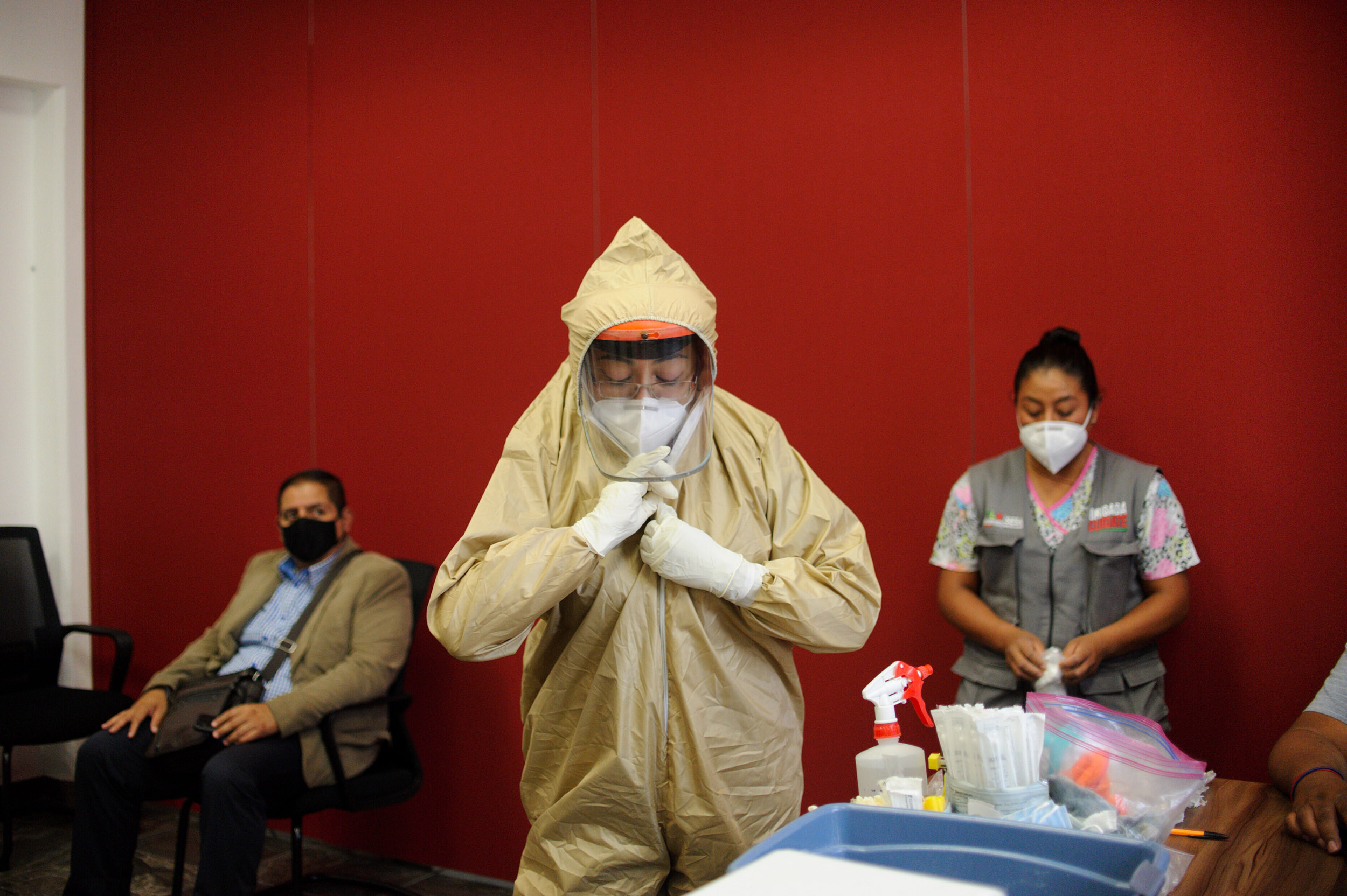 A health care worker puts on a protective suit before submitting members of the Tlaxcala State Congress to a Covid 19 test on August 10.