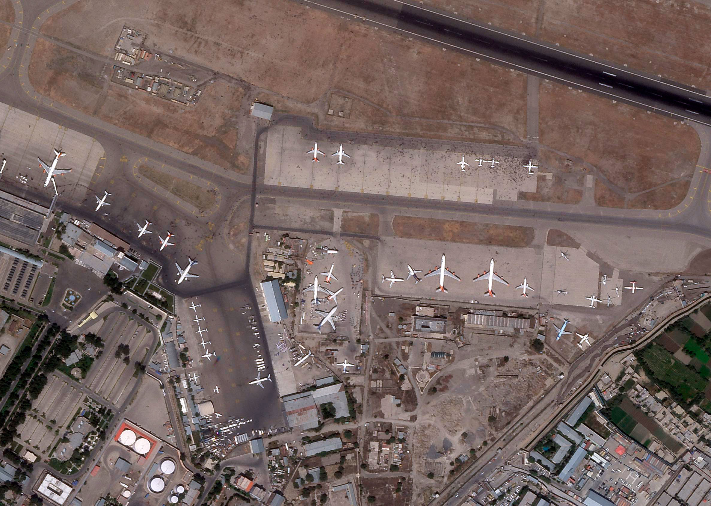 This satellite image from Planet Labs shows people on the tarmac at Hamid Karzai International Airport in Kabul, Afghanistan, on August 16, 2021.