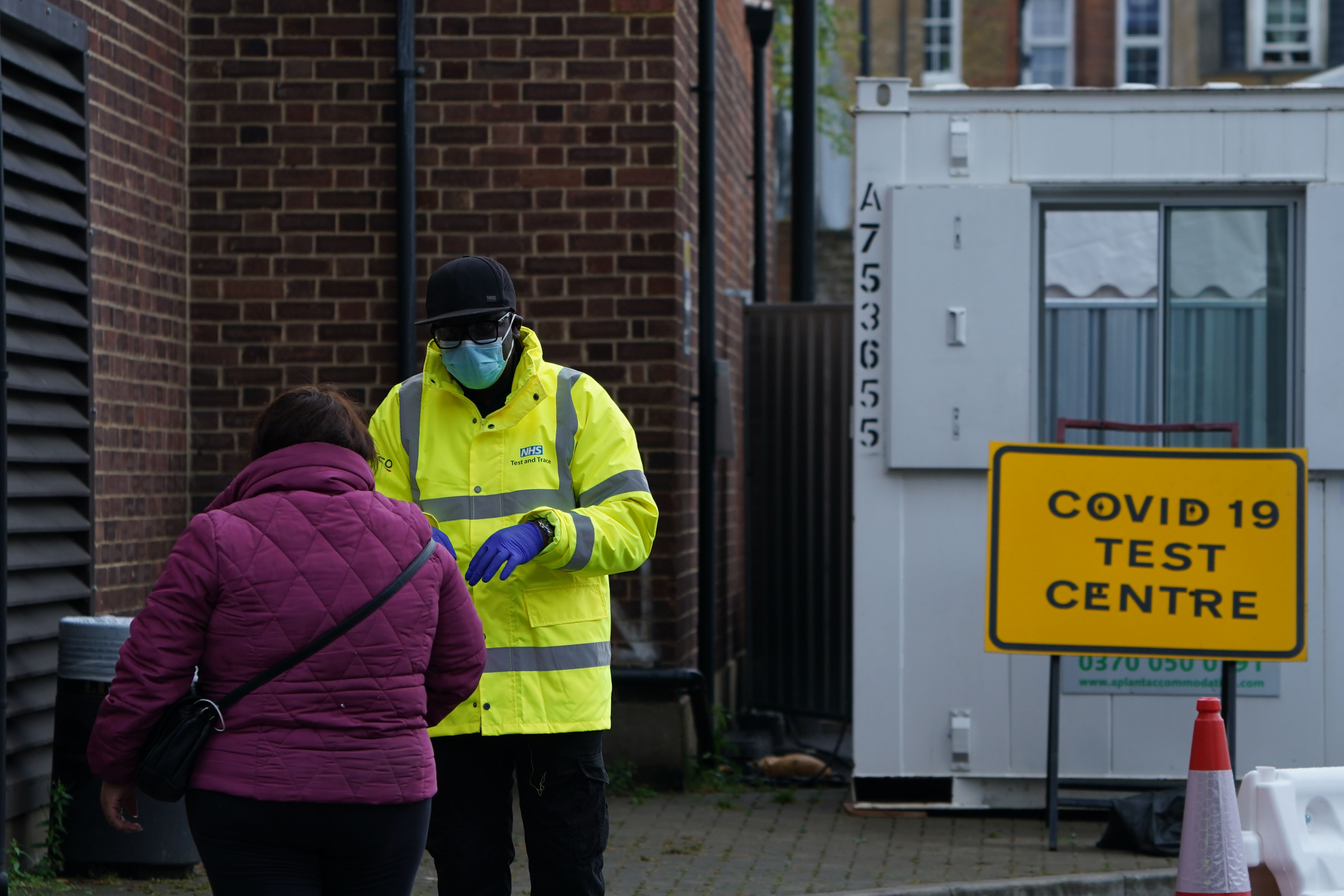 A NHS employee speaks to a member of the public outside a Covid-19 testing center in Dalston, east London, on September 23.