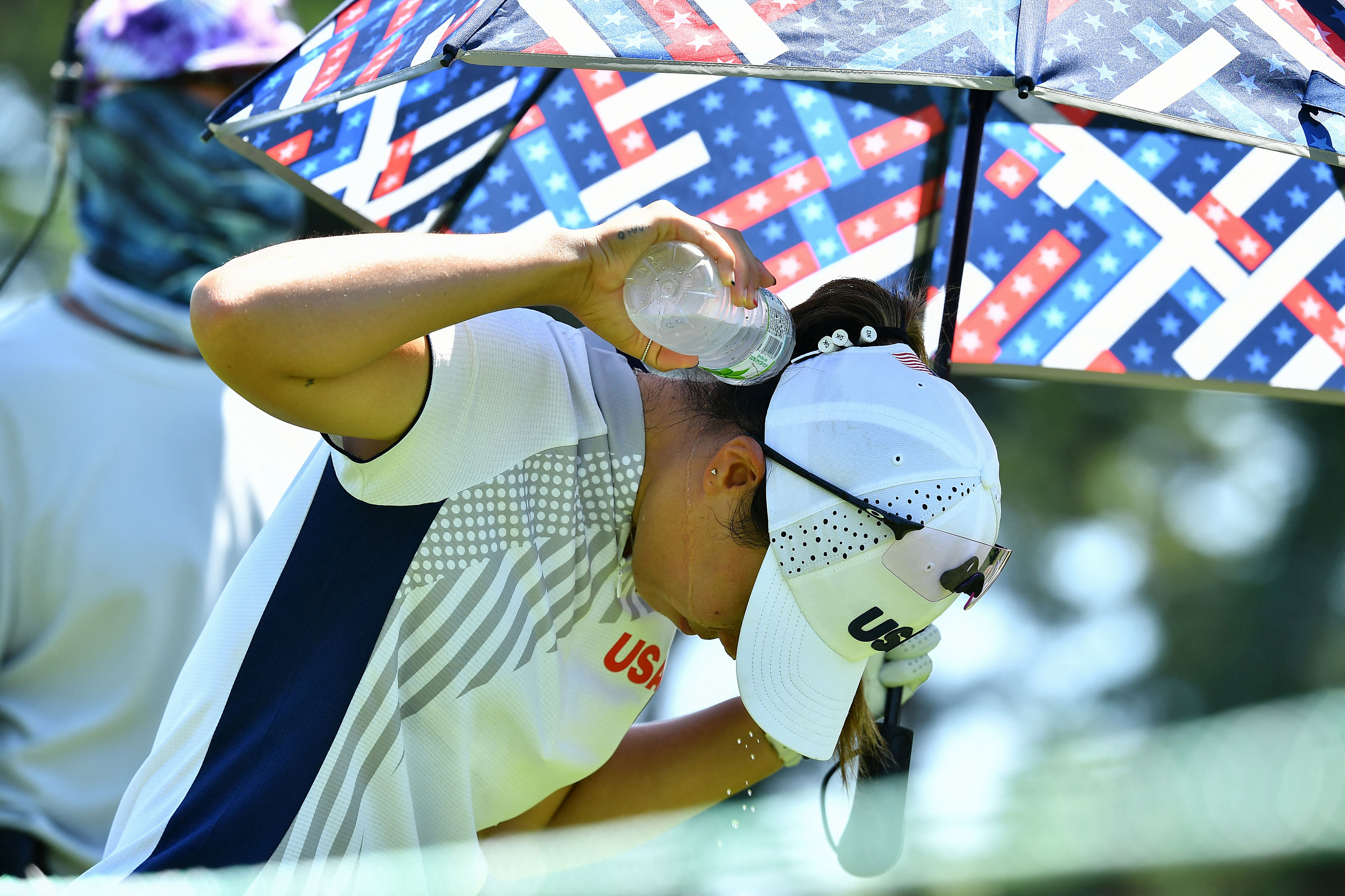 American golfer Danielle Kang throws water on her neck to cool off in round 1 of the golf individual stroke play on Wednesday, August 4.